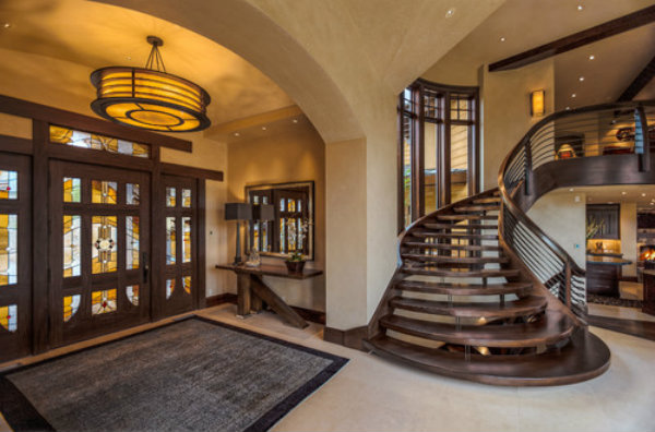 The amber glow from a Hammerton contemporary drum chandelier and wall sconce gives this modern craftsman entryway a welcoming warmth.