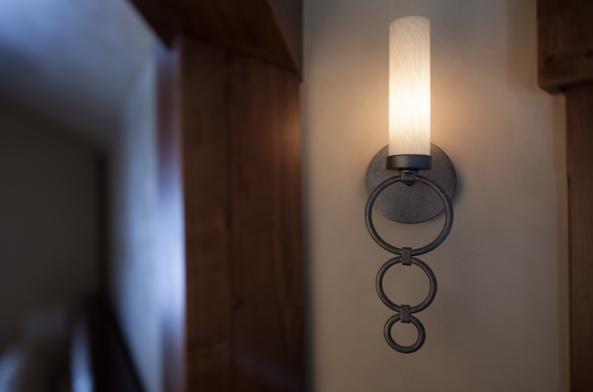 Also used as accent lighting in the hallway is an understated sconce with a light blown glass cylinder and pewter finish.