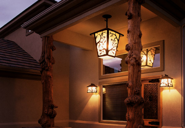 A Log & Timber chandelier with a maple branch motif and matching wall sconces coordinate perfectly with a rustic exterior.