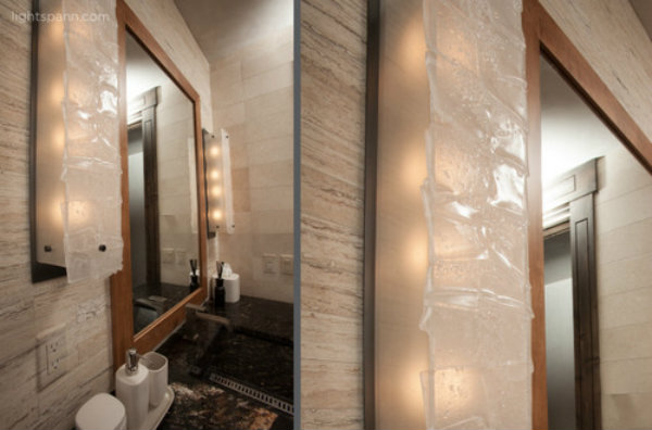 Textured glass can create visual interest for functional task lighting. Most designers recommend using incandescent bulbs in the bathroom to produce complexion-flattering effects.