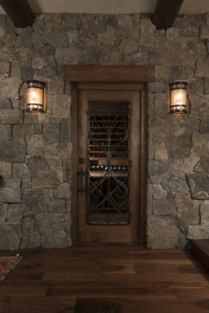 A pair of mica wall sconces gives this wine room entrance a warm, luxurious vibe.