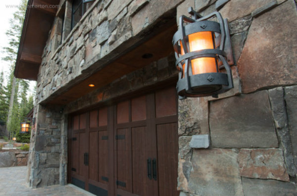 The antique iron finish on this outdoor light fixture nods to the beautiful palette of natural wood and stone materials in this garage facade..