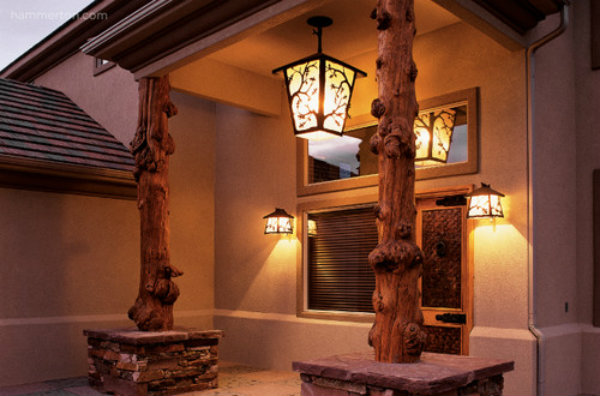 Matching outdoor wall sconces and a pendant fixture from the Hammerton Log & Timber Collection beautifully complement the burly posts in this rustic entryway.