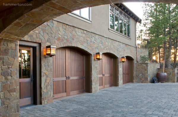 A row of traditional outdoor light fixtures from Hammerton's Chateau Collection adds a sense of old world sophistication to this garage facade.