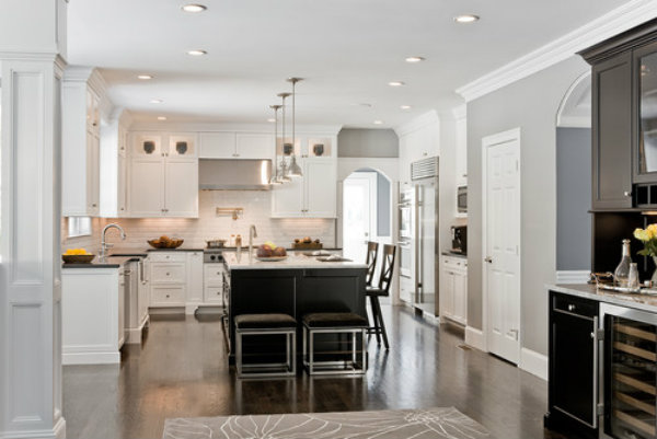 This kitchen features recessed lighting, task lighting under the cabinetry, as well as three overhead light fixtures above the kitchen island. In combination with the reflective white finishes, these help boost energy and functionality in a high traffic area.