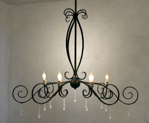 The Lightspann Lucien Chandelier offers a uniquely elegant design featuring hanging glass crystals carefully crafted to look like drops of water. The delicate nature of the droplets echo the chandelier's graceful curves and curls.