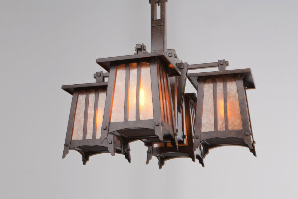This custom Craftsman chandelier is crafted with mica glass and a dark bronze finish. You can certainly see the architectural inspiration from Greene and Greene -- the strong tapered sides and articulate horizontal lines give this fixture a bungalow feel, as well as sculptural prowess.