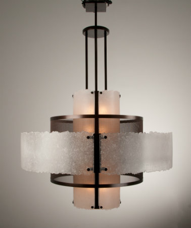 This show-stopping chandelier features graceful layers of fine woven steel mesh and slumped fused crystal glass. Rough edging of the glass panels add textural interest and underscore the fixture's artisanal nature.