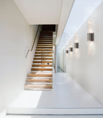 The warmth of this wooden staircase is complemented by our Bamboo sconces, which reflect a sophisticated light pattern on the surrounding wall and add a sculptural element to this modern, minimalist space.