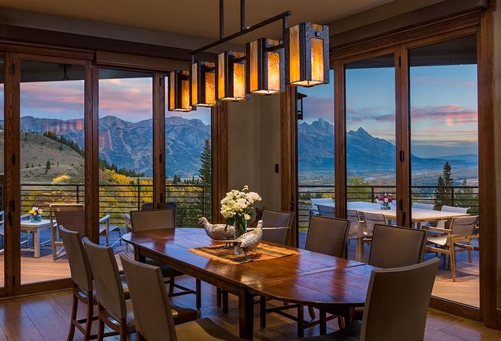A custom Hammerton contemporary dining light in dark art glass and hammered steel enhances the sweeping postcard view of this Wyoming dining room. By Trynity DeVries Interior Design | Bozeman, MT