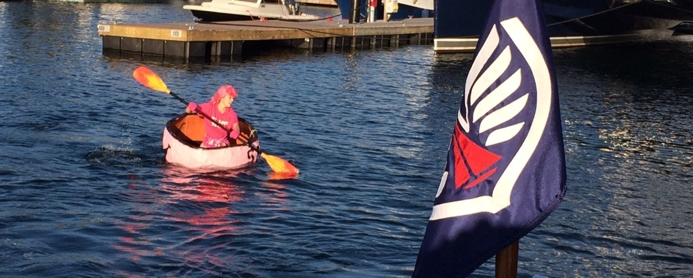 Jess from Belle's Cafe paddles across the inner basin as part of Newport Shipyard's annual Pink Pumpkin Regatta to raise money for breast cancer awareness.
