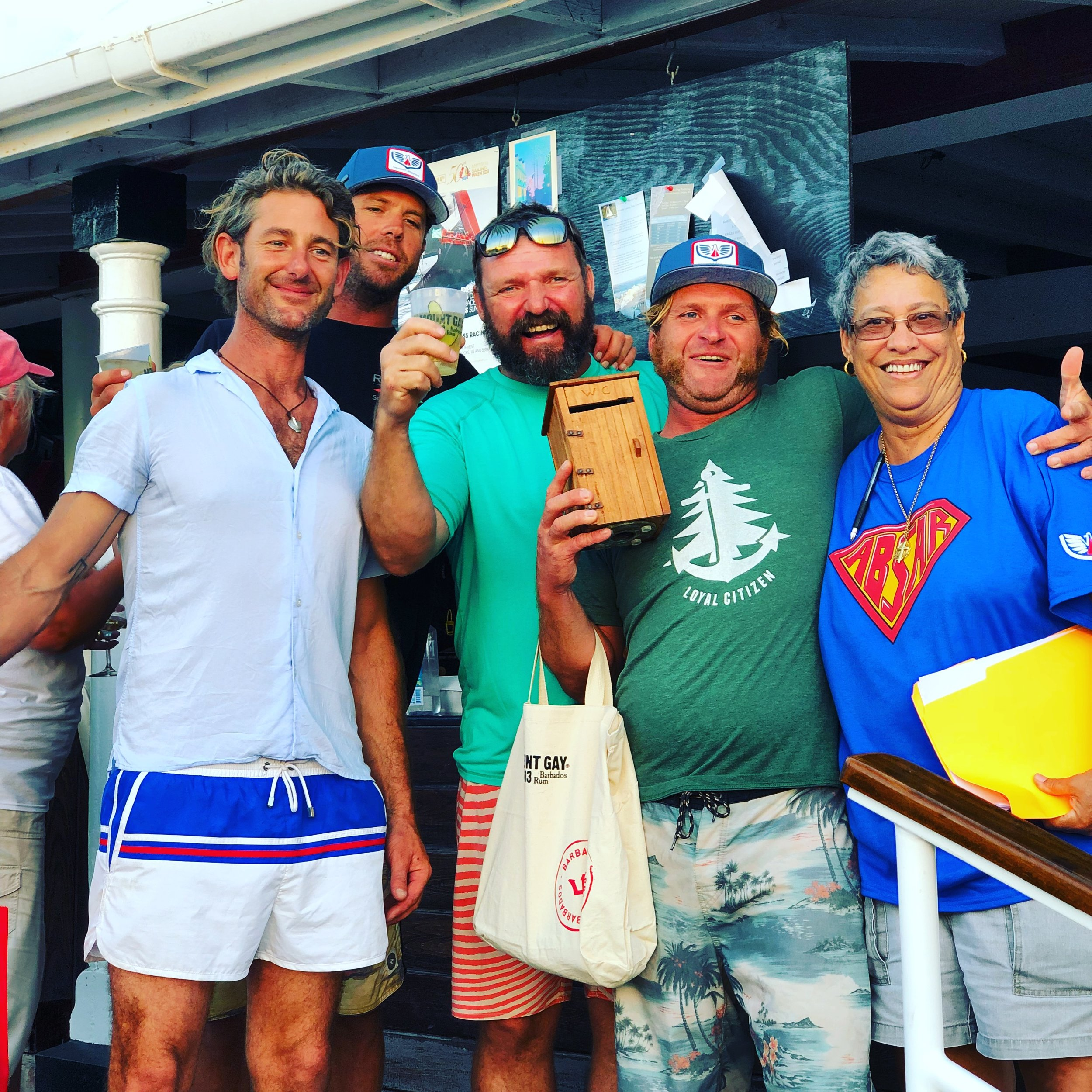 From L-R: J Class yacht  Topaz  crew members Bill Hitchins, Ian Aitchison, Captain Rom Loopik, and Mate Nat Lemieux,accept the overall Wobbly Race award in Antigua in February from Catamaran Marina dockmaster Helen Bailey.