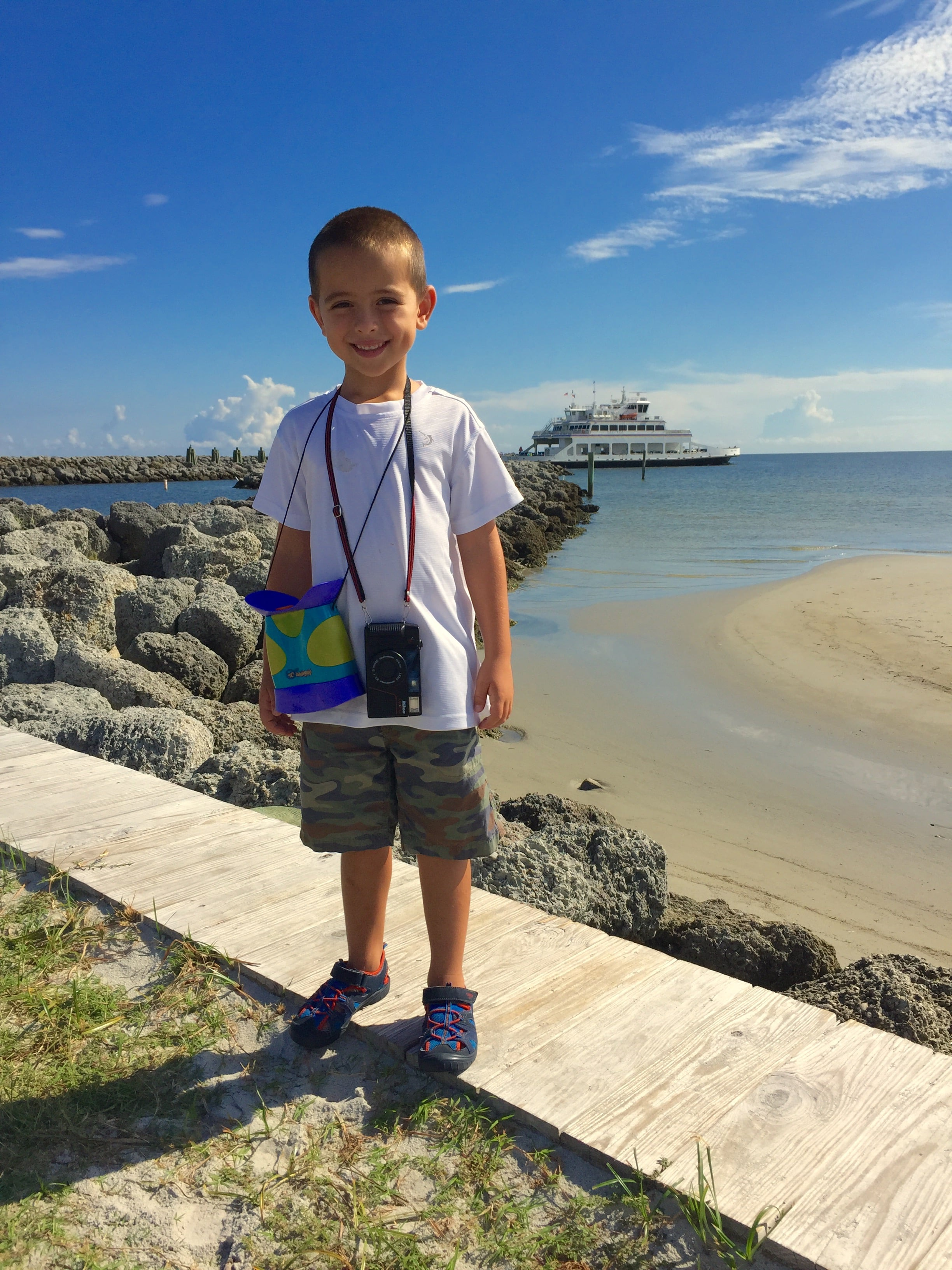 At five years old, adventuring at Cedar Island with his binoculars and 35mm rangefinder. 2015.