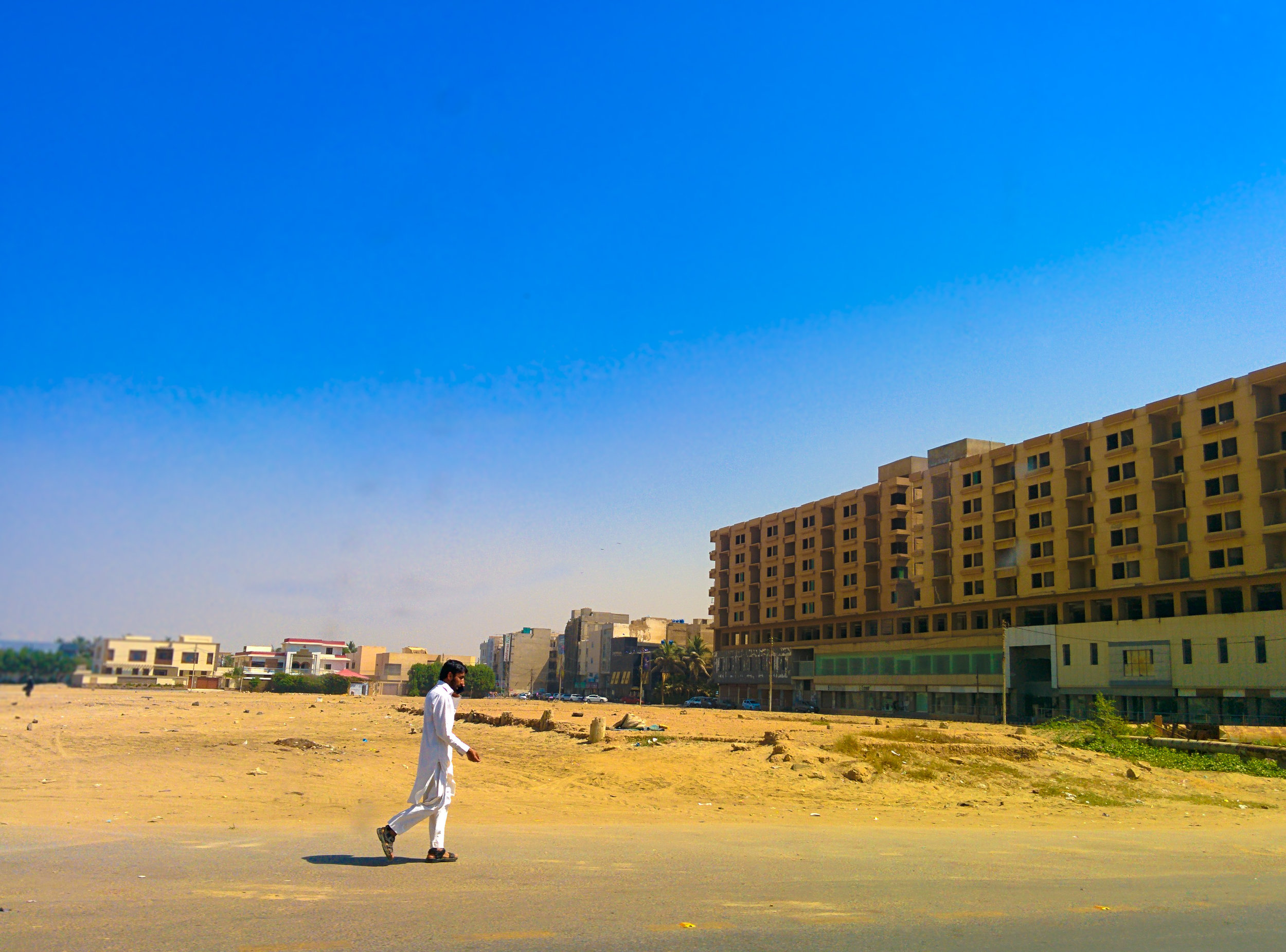 A local pedestrian crosses the road in the sweltering heat.