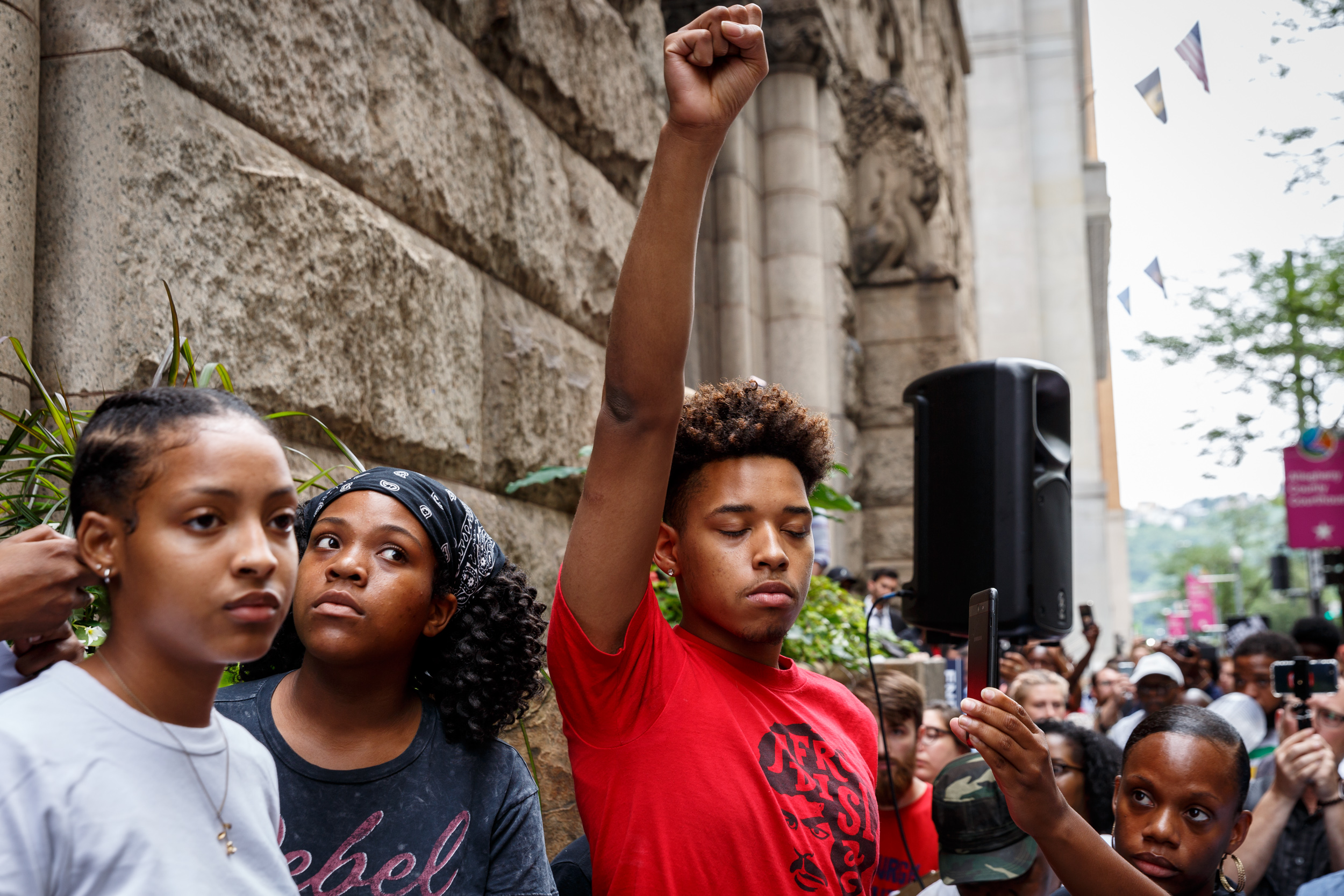 "Christian Carter, 18, a member of the Youth Power Collective, raises his fist in the air in protest of Antwon Rose Jr.'s death. Carter later read a poem Antwon wrote: ""I wonder what path I will take/I hear that there's only two ways out/I see mothers bury their sons/I want my mom to never feel that pain."""