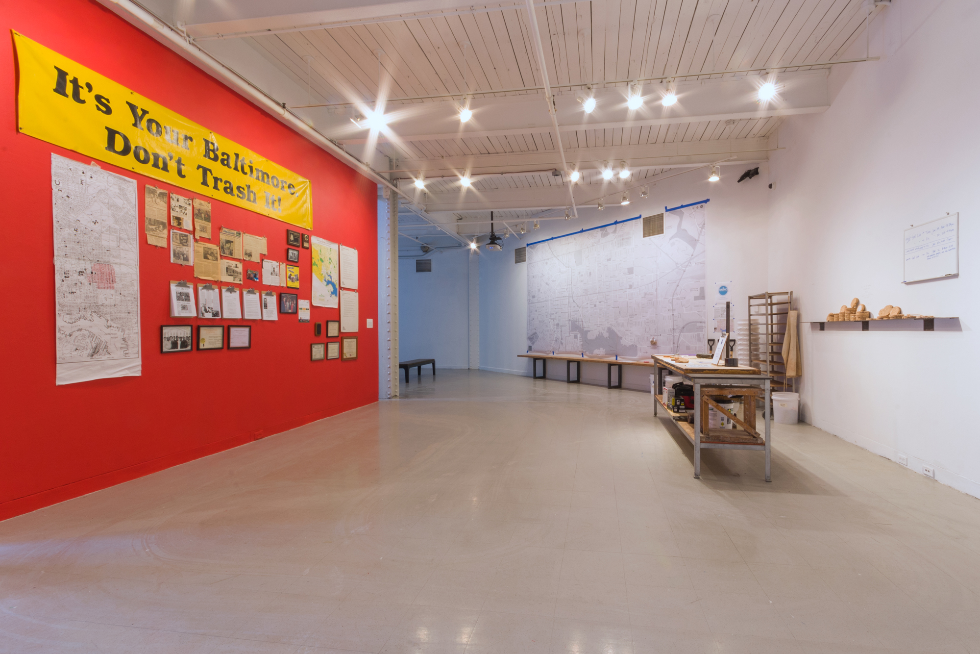 Installation shot featuring assorted archival material from Glenn Ross, 1984 – 2018, and Margaret Boozer/Raina Märtens + UnInc.,  Soil Lab: Toxic Tour Beer Coasters,  workbench, table, buckets, maps, shovels, soil samples, various tools, 2018