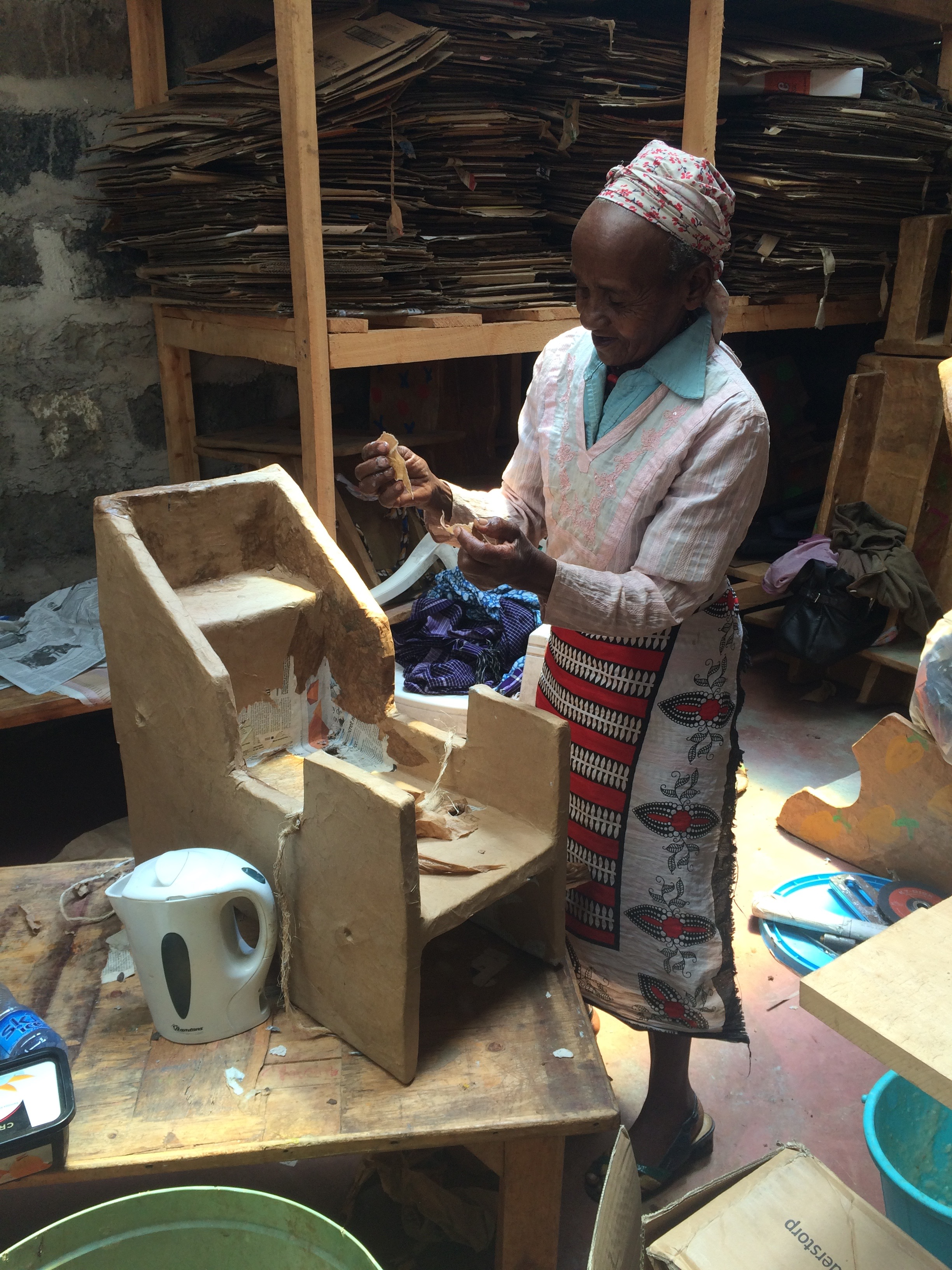 Granny Munene, who is employed at the SanctuaryArtists workshop, building one of the assistive cardboard chairs.