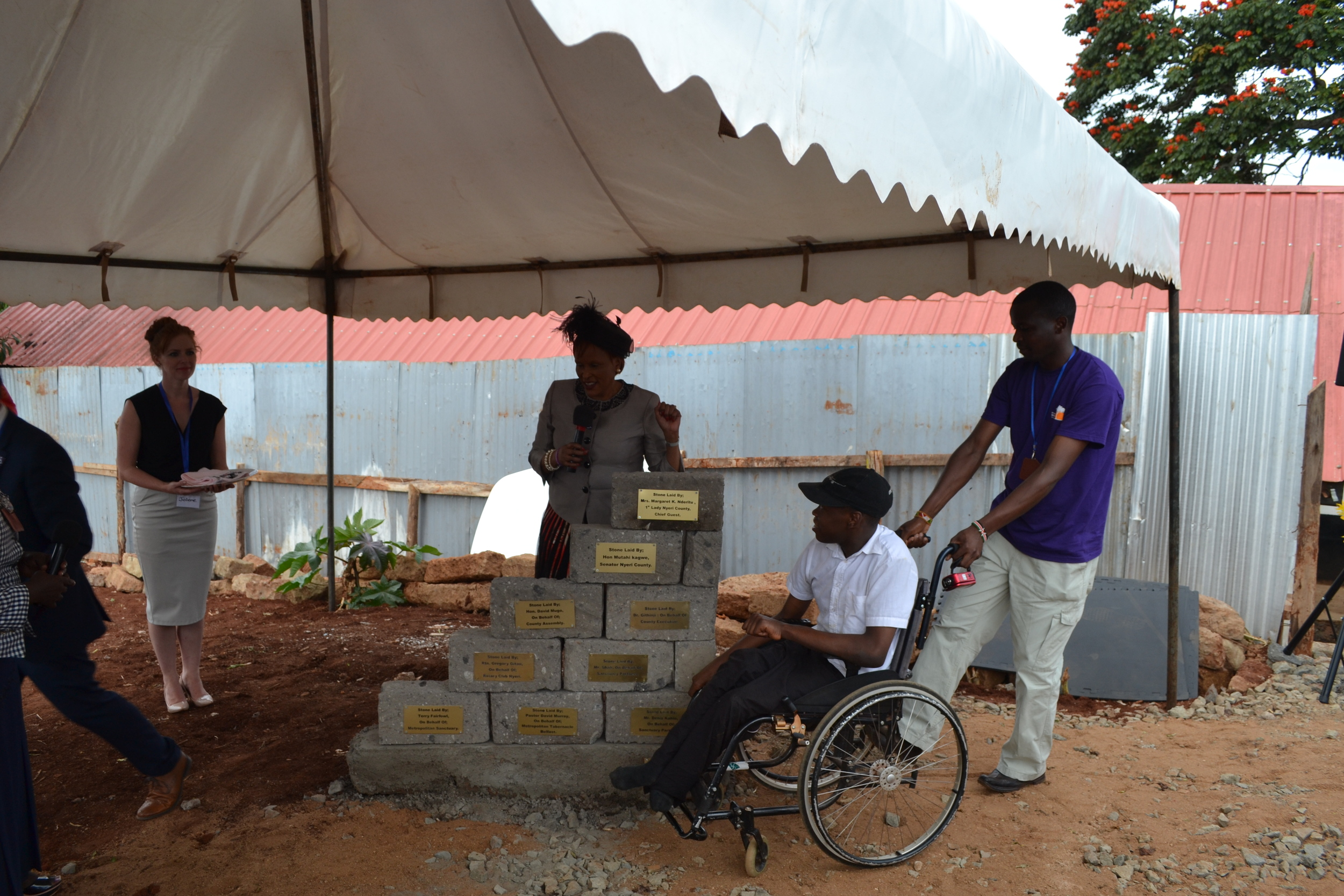 The First Lady of Nyeri County lays a foundation stone, accompanied by Dennis who attends the Metropolitan Sanctuary for therapy and day care.