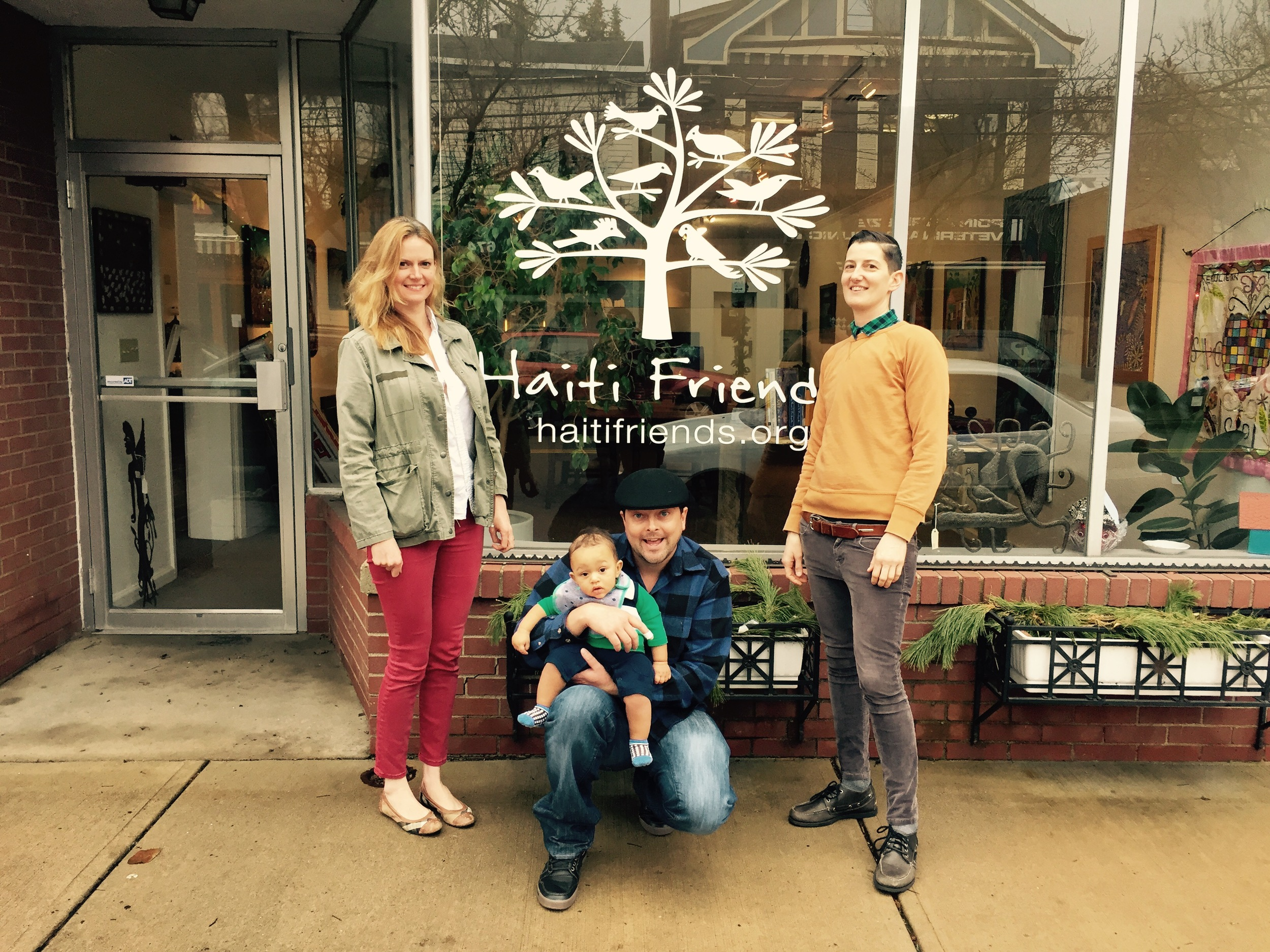 Deputy Director Bee (right), Program Associate Caitlin (left), and Executive Director Eddie with his son Olivier (center) in front of the new sign at the gallery on Reynolds St.