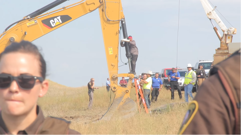 A DAPL protestor locks himself to construction equipment. August 31, 2016, North Dakota. Desiree Kane [CC BY 3.0 (http://creativecommons.org/licenses/by/3.0)], via Wikimedia Commons