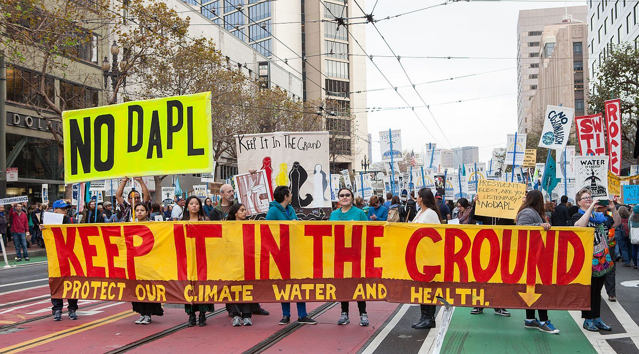 November 15, 2016: People protesting the Dakota Access Pipeline stand in the street with signs and banners. By Pax Ahimsa Gethen - Own work, CC BY-SA 4.0, https://commons.wikimedia.org/w/index.php?curid=53199437
