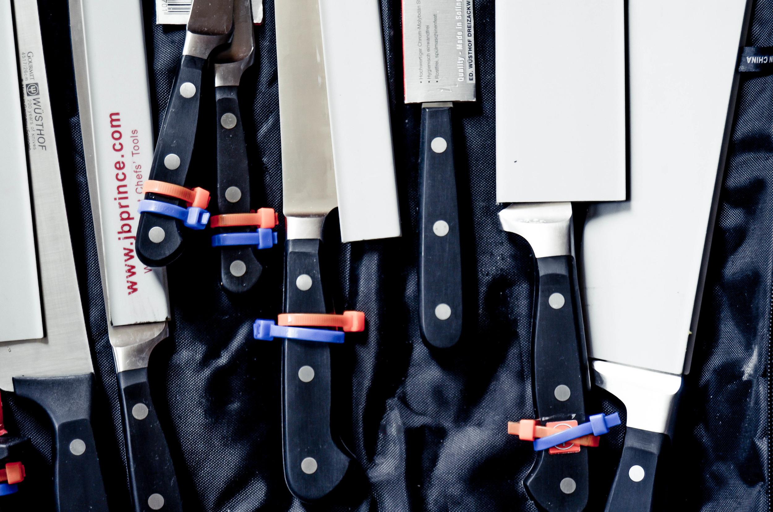 "left to right: chef's 10"" knife, filet knife, tourne, paring, santoku, turning fork, boning, bread."