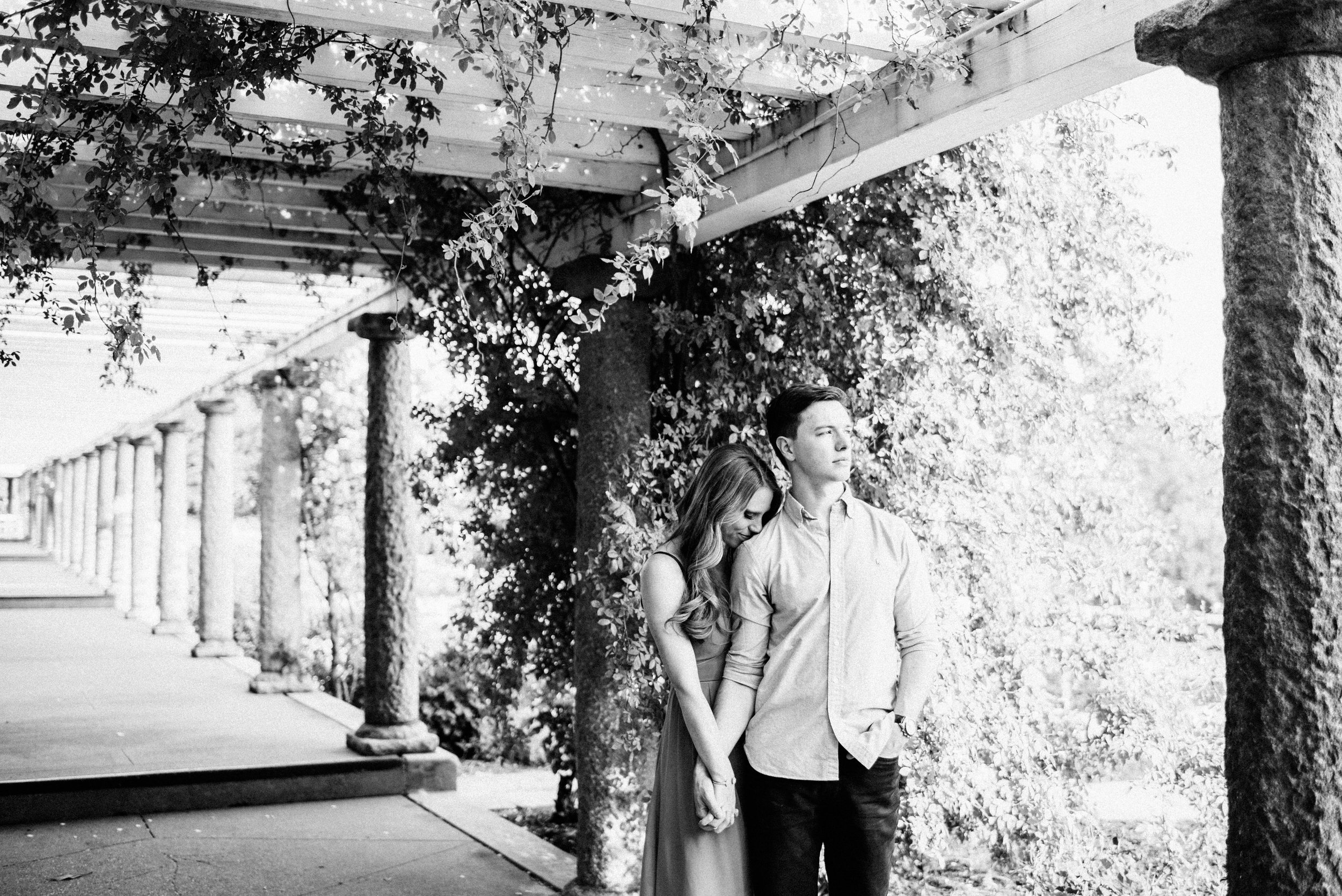 black and white engagement photo with pergola