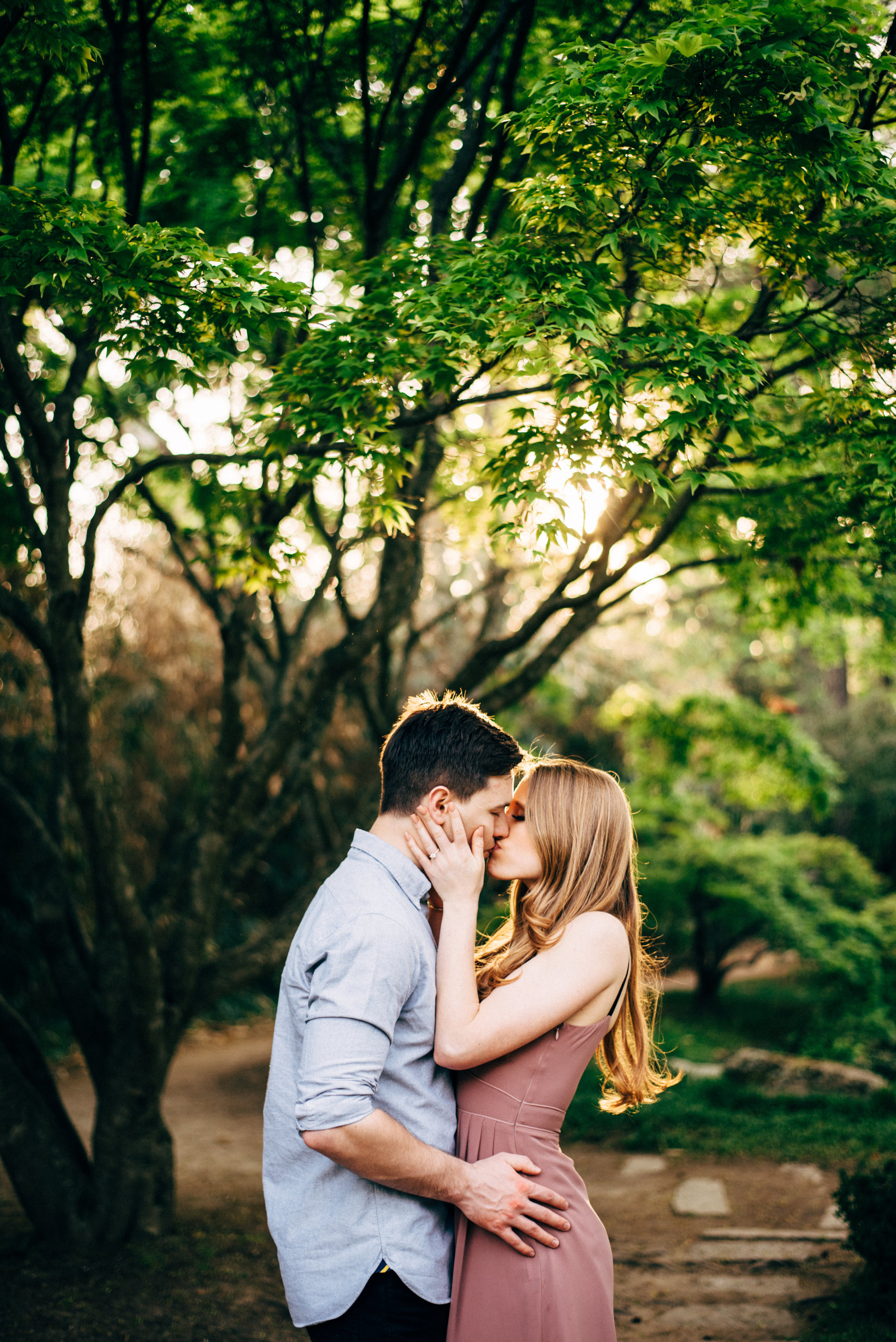 park engagement kissing beneath trees
