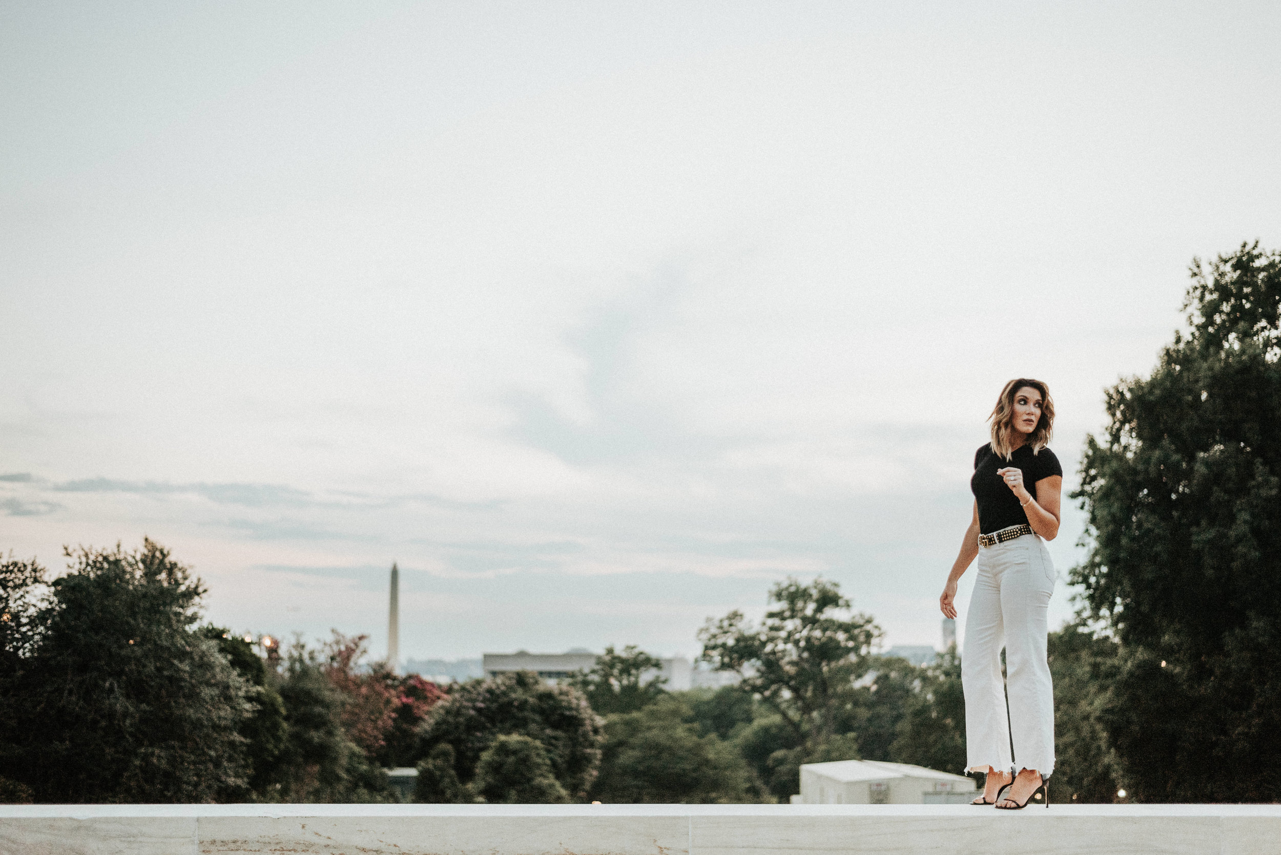 woman standing on ledge with Washington Monument in the distance