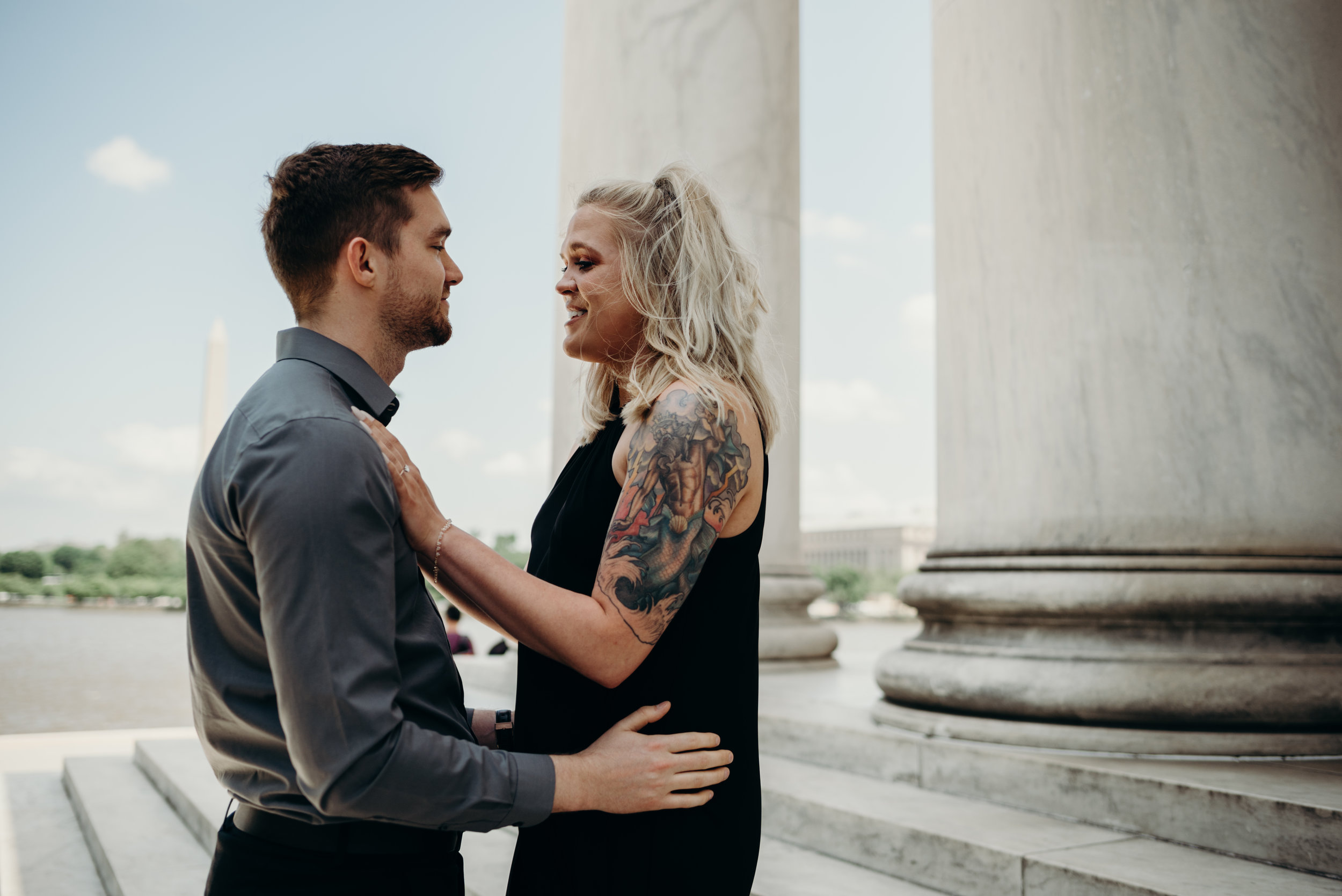 Man and woman looking at each other on steps of Thomas Jefferson Memorial with the Washington Monument in background