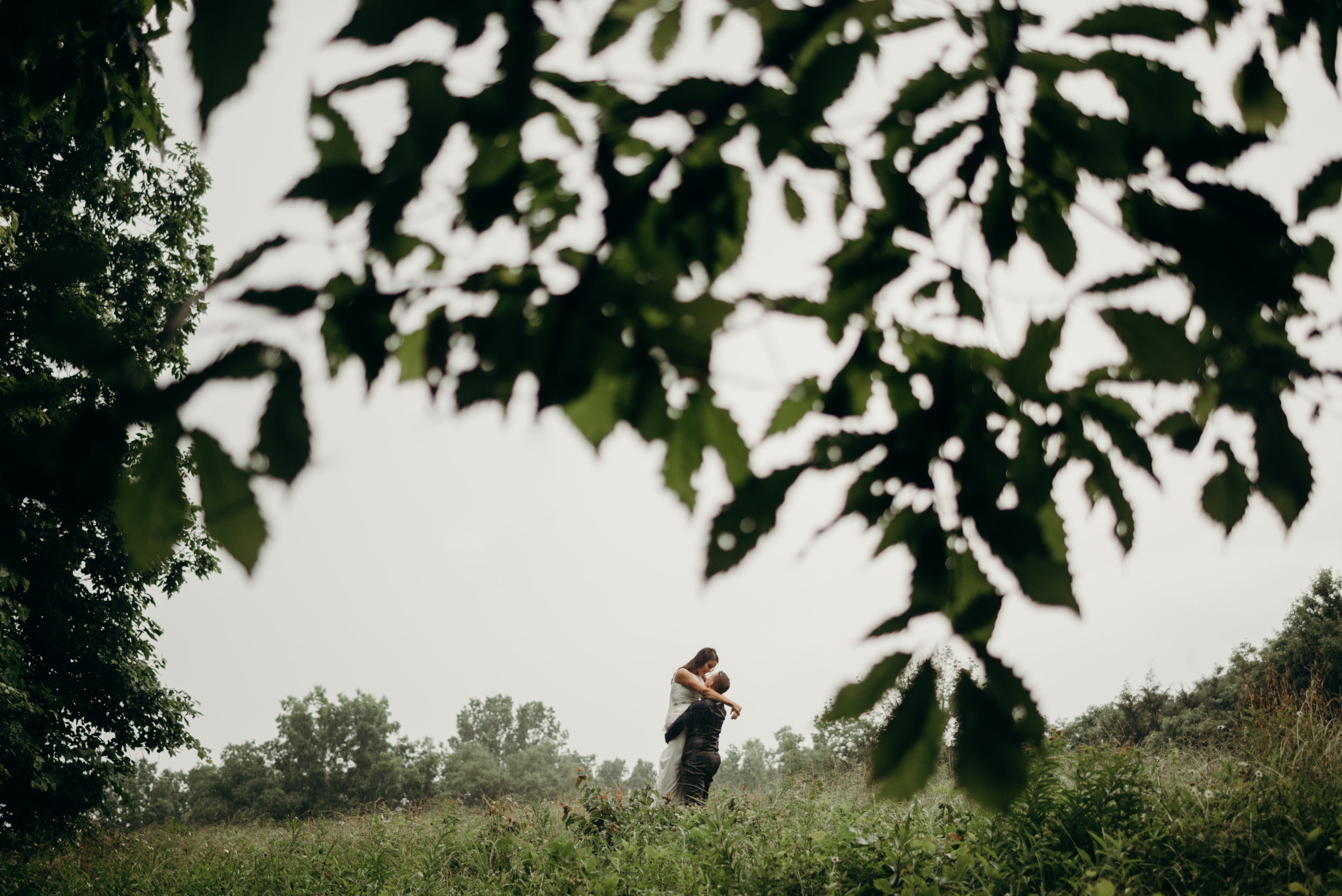 woman in suit lifting her wife into the air in a Kentucky field