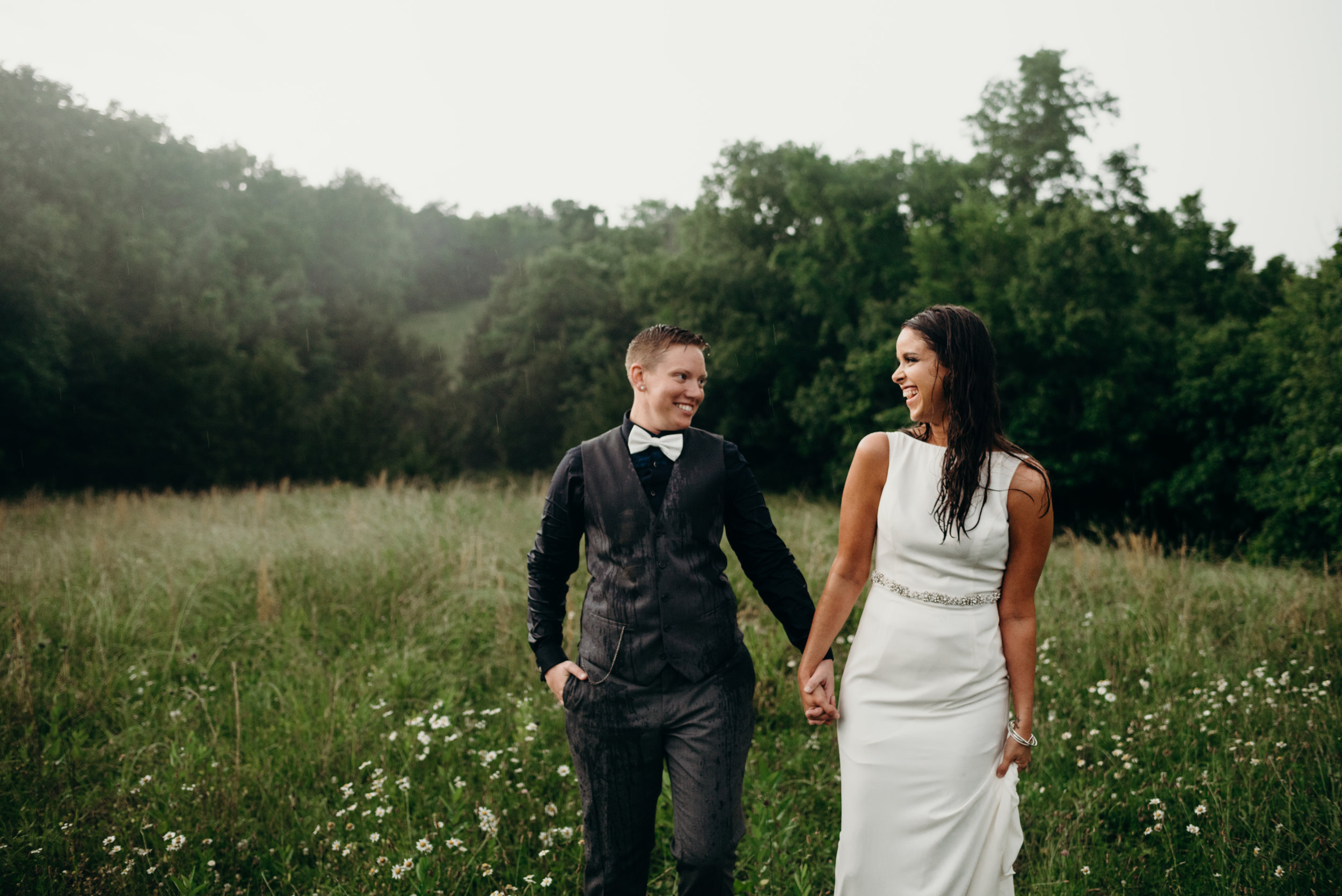 post-wedding photography session with newlywed couple holding hands and smiling at each other while walking in a field