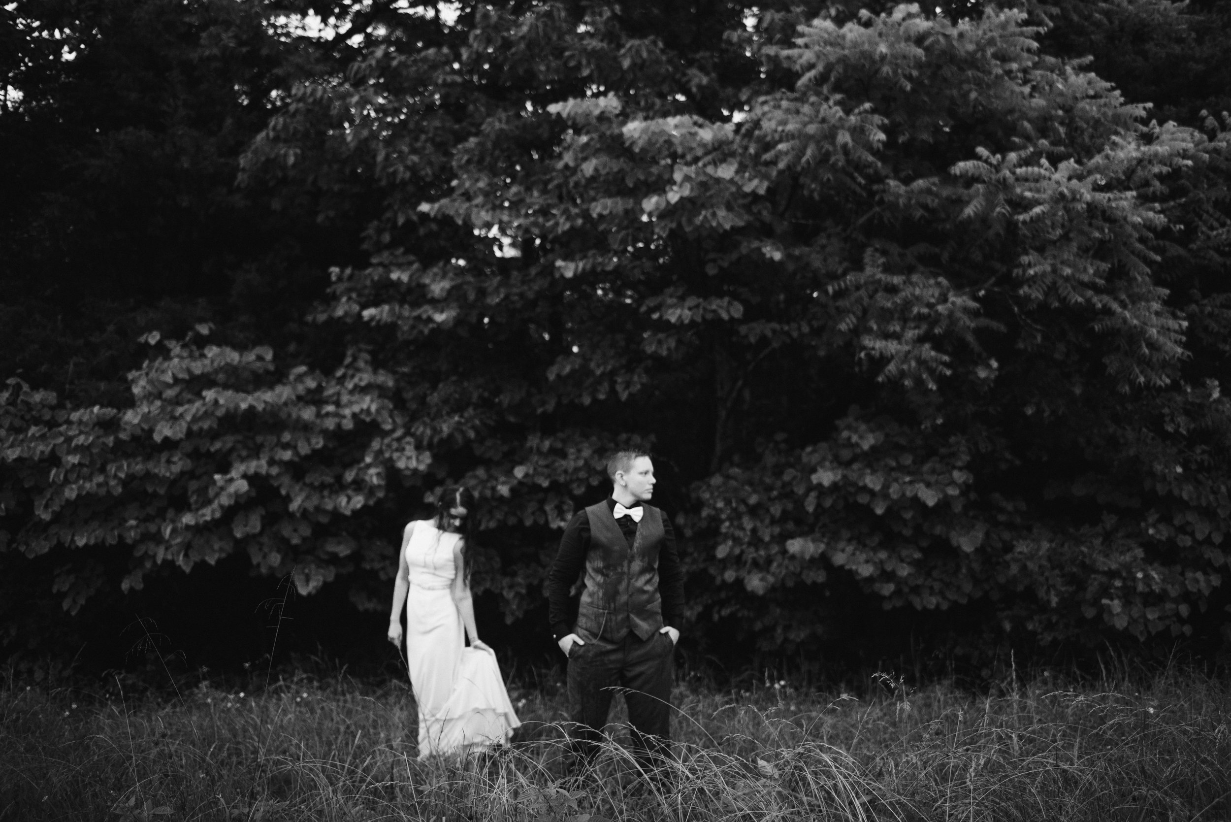 post-wedding session with two women posing in wedding attire in field with trees behind them