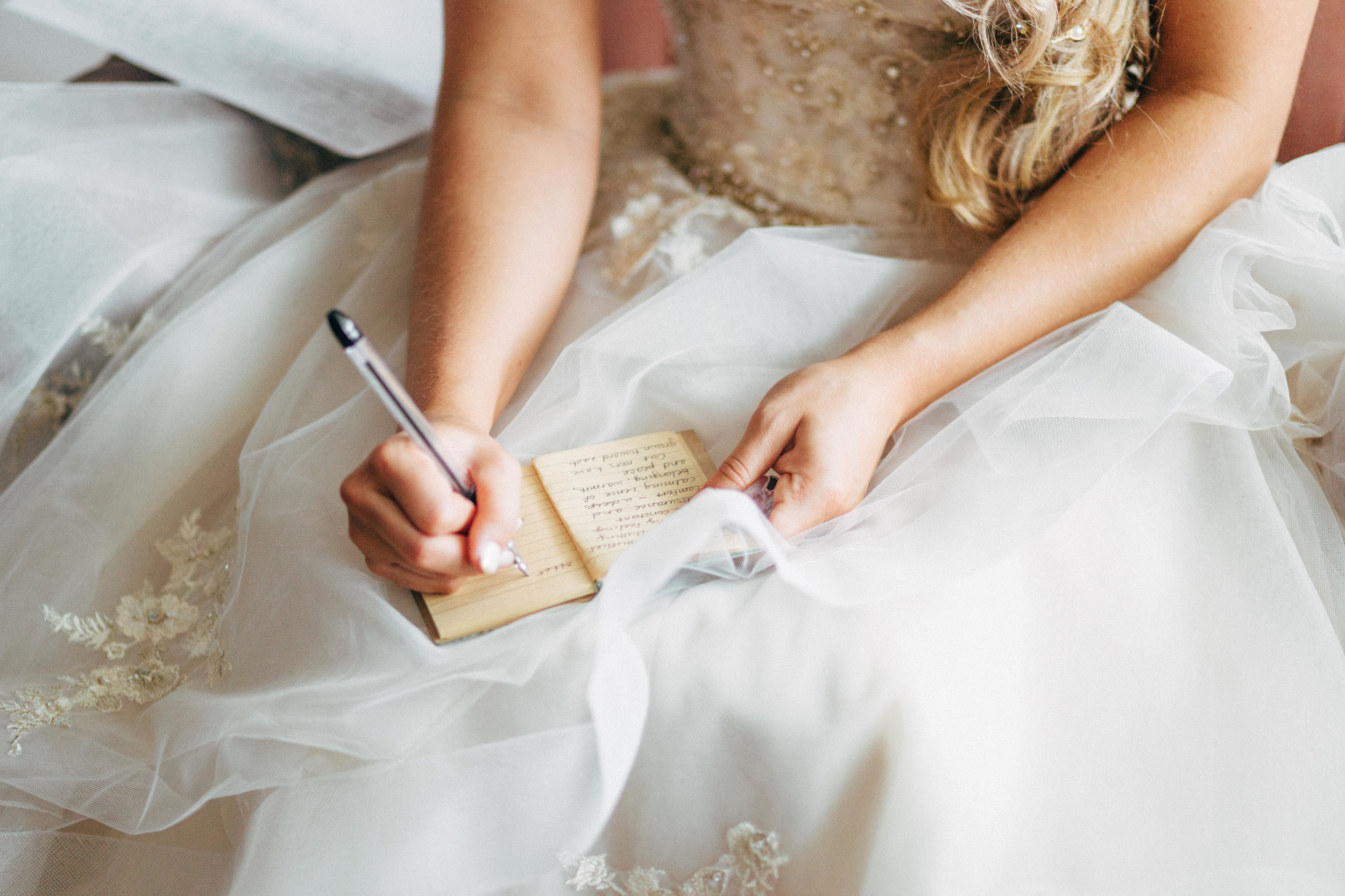 bride in wedding dress writing letter to her groom before wedding