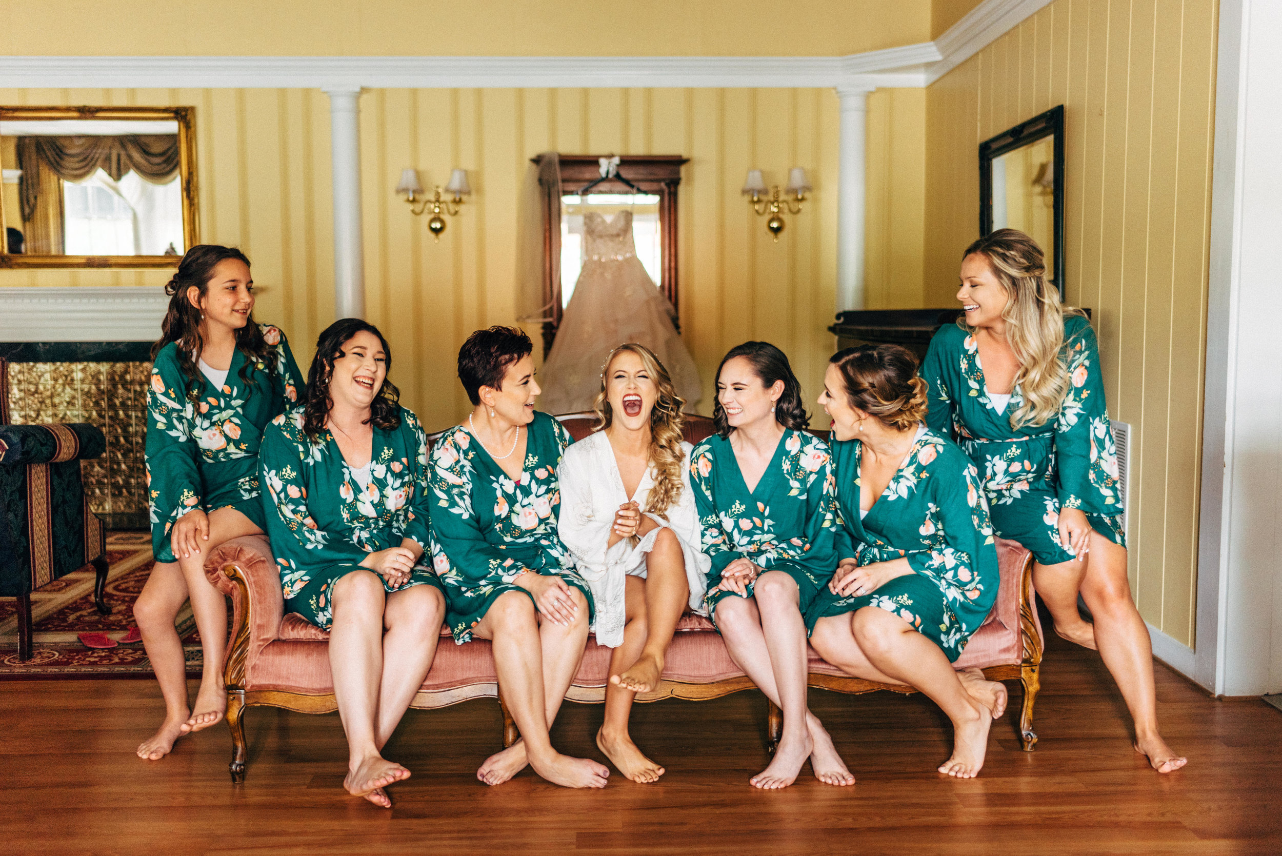bride laughing with her bridesmaids on couch before wedding