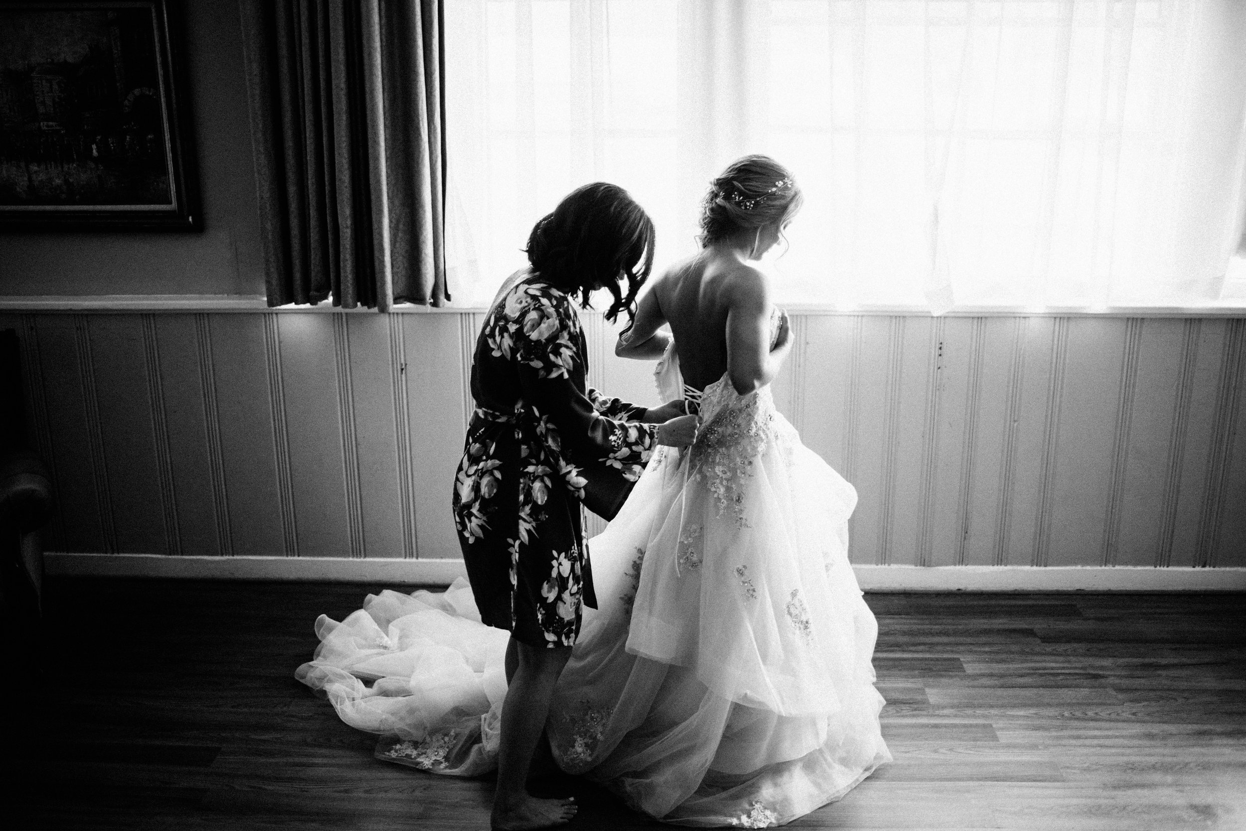 black and white photo of bridesmaid lacing up the back of bride's wedding dress