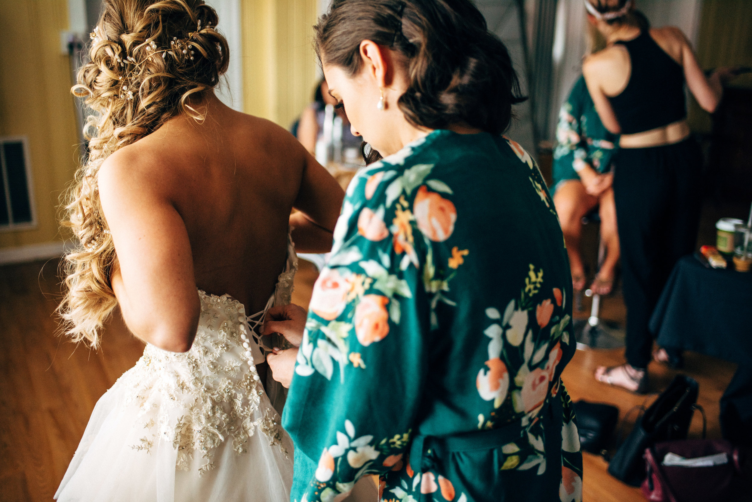 bridesmaid lacing up bride's wedding dress