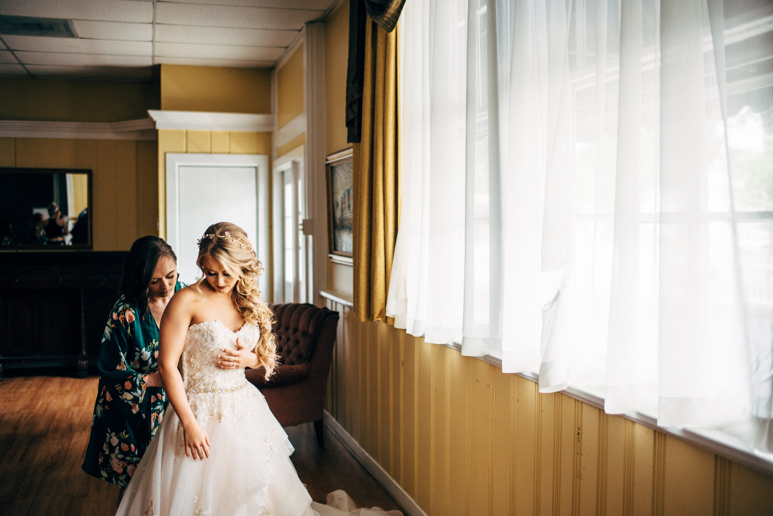 bridesmaid helping bride with her wedding dress in front of window at The Inn at the Old Silk Mill