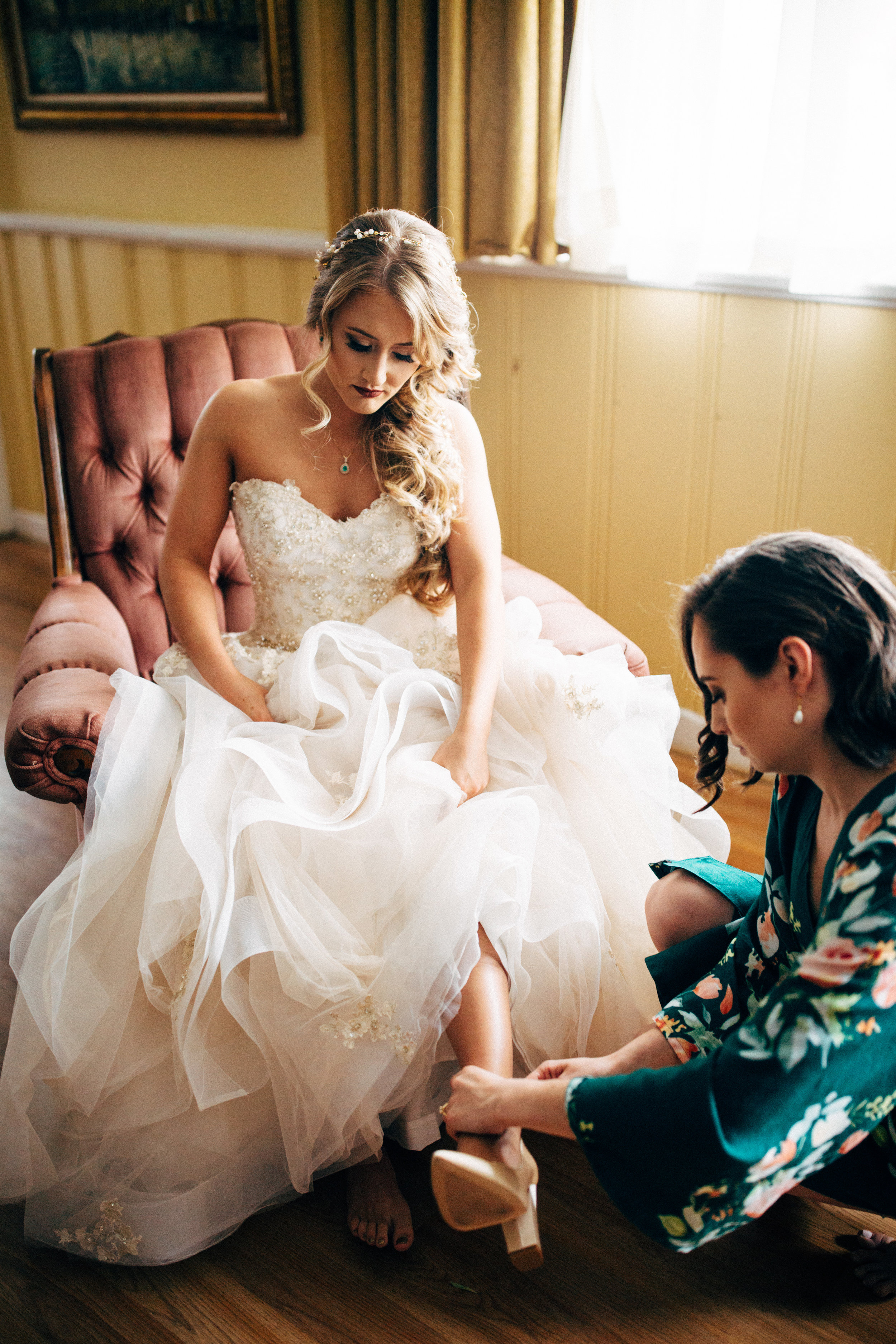 bridesmaid putting shoe on fairy-tale bride's foot before wedding