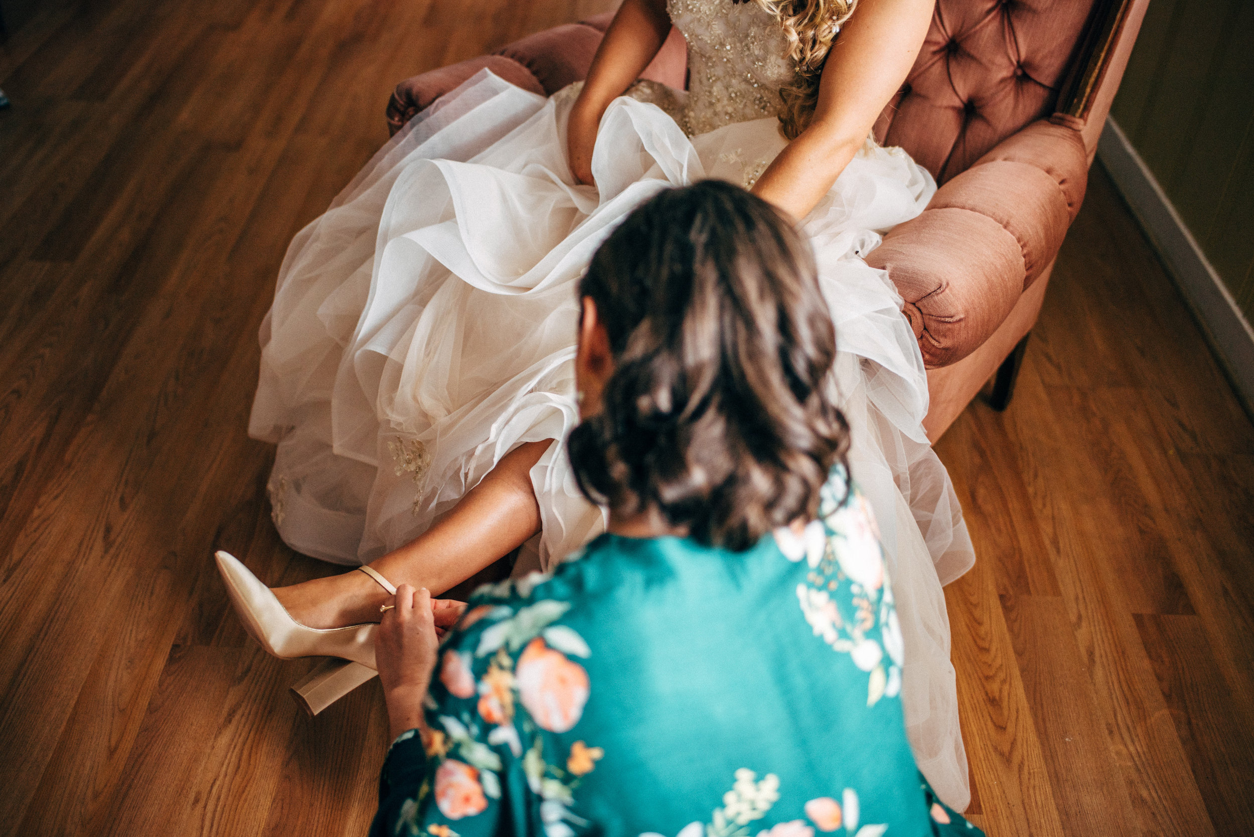 bridesmaid putting shoe on bride's foot before wedding