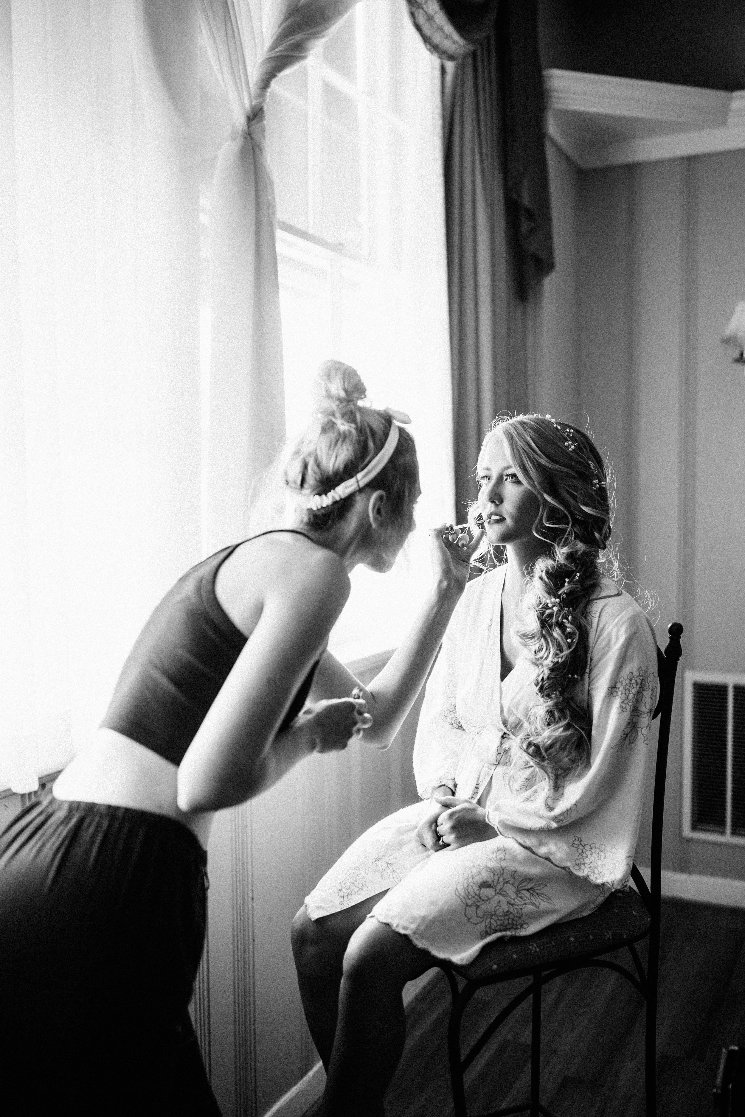 black and white photo of makeup artist putting lipstick on bride before the wedding