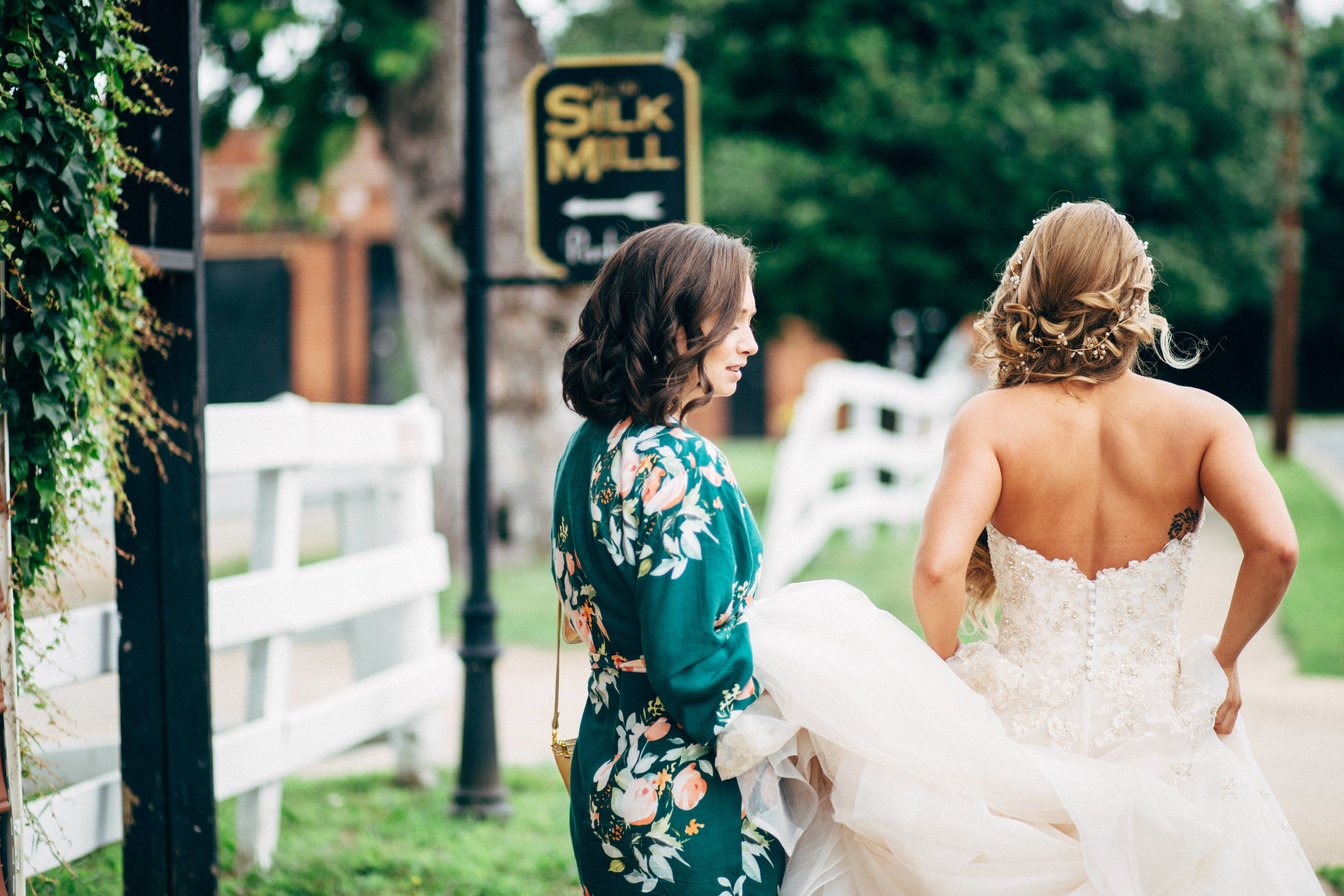 bridesmaid holding back of bride's dress on path at The Silk Mill Fredericksburg Virginia