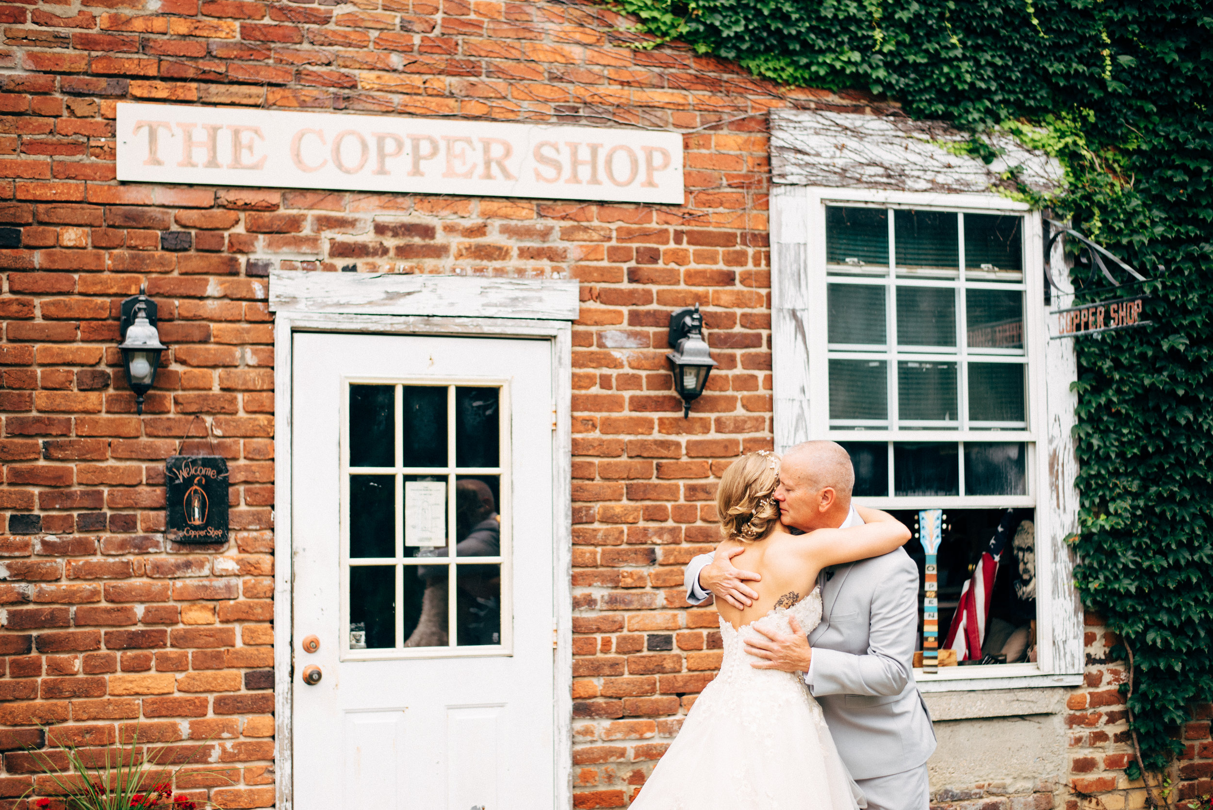 father and daughter embrace on wedding day with brick building behind them