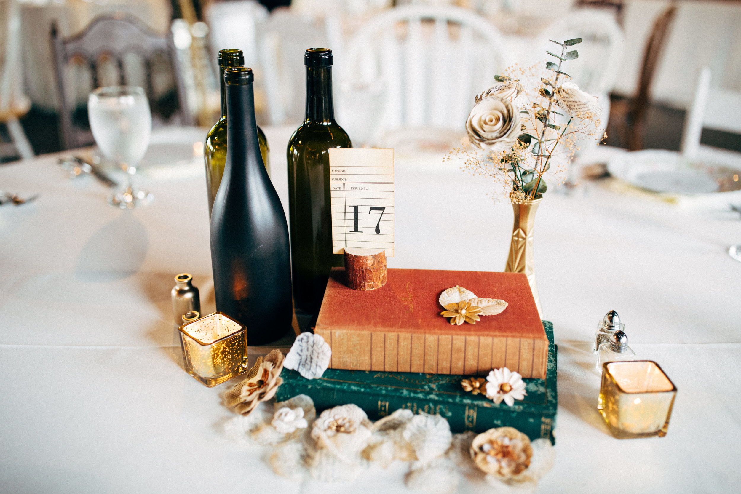 tables at wedding reception decorated with wine bottles, flowers, books, and table number library card
