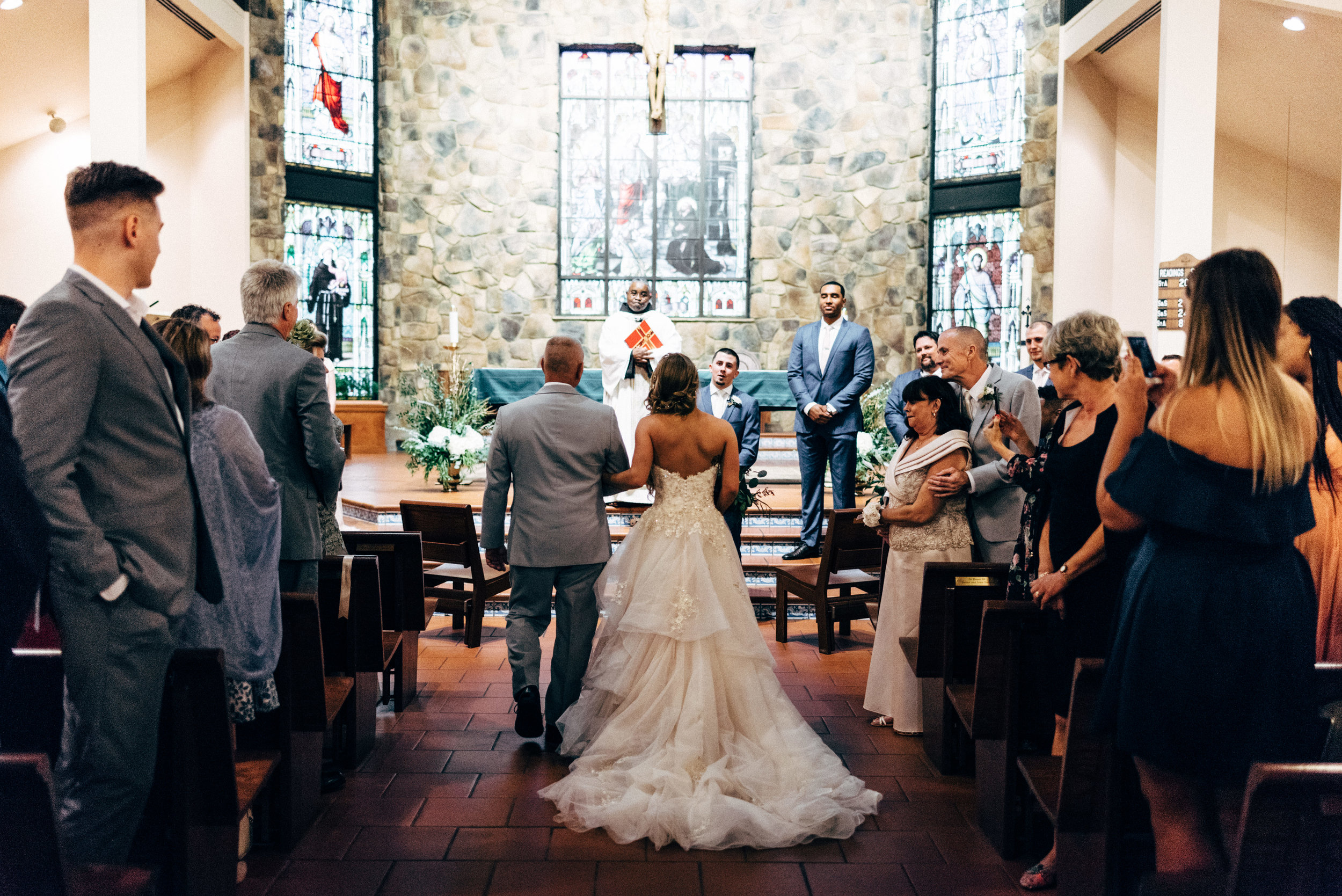 father giving away the bride at wedding inside St. Francis of Assisi Catholic Church