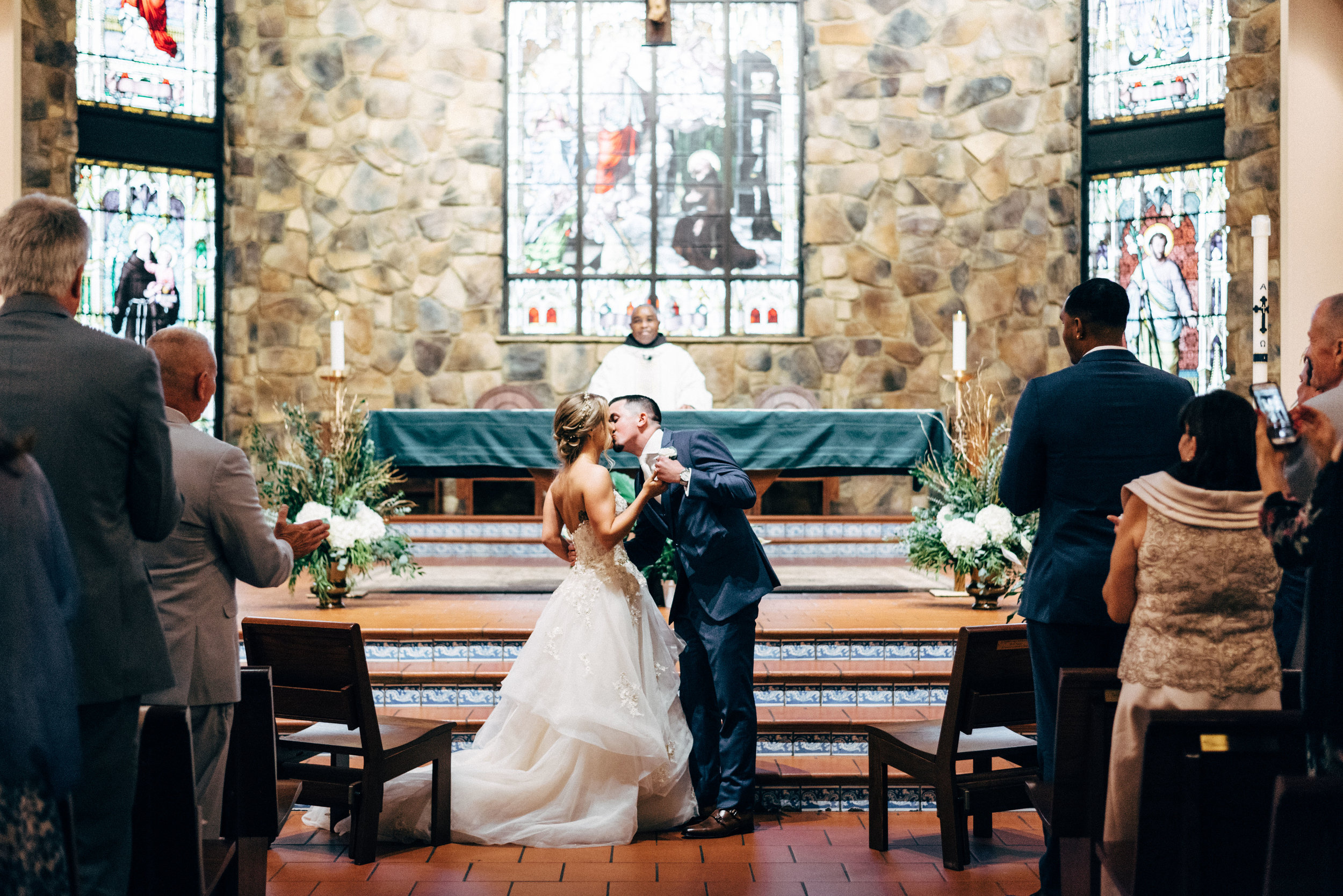 groom kissing his bride during wedding ceremony at St. Francis of Assisi Catholic Church