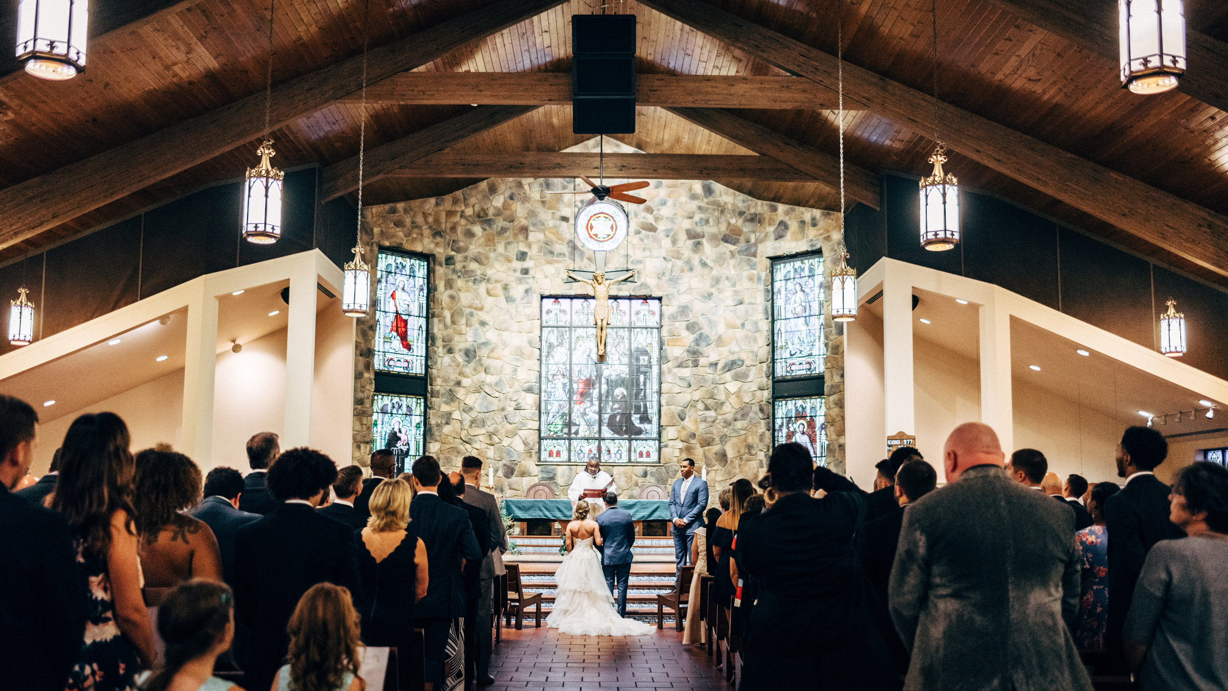 bride and groom standing in front of priest at St. Francis of Assisi Catholic Church
