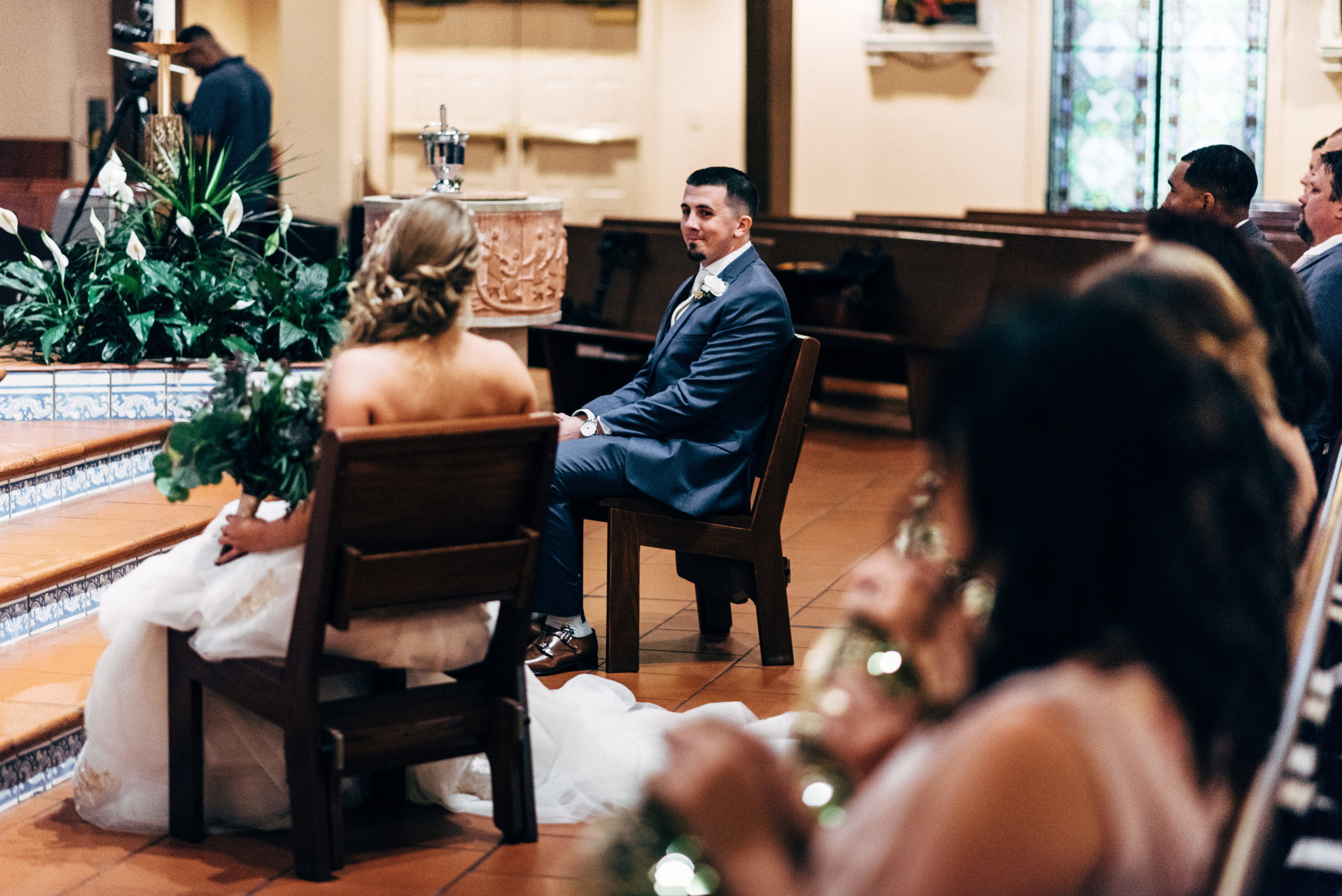 bride and groom sitting during wedding ceremony at St. Francis of Assisi Catholic Church