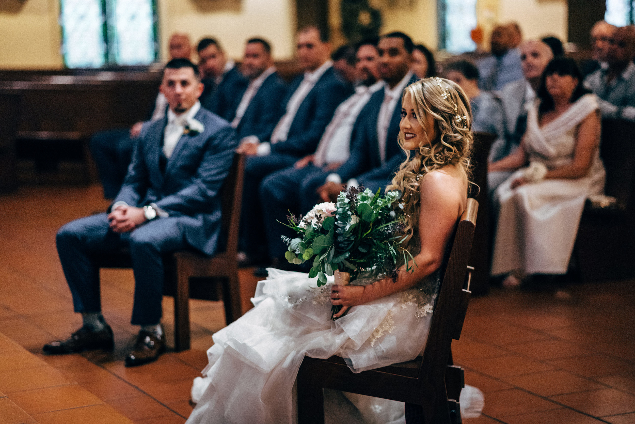 bride holding her bouquet while sitting during wedding ceremony at St. Francis of Assisi Catholic Church