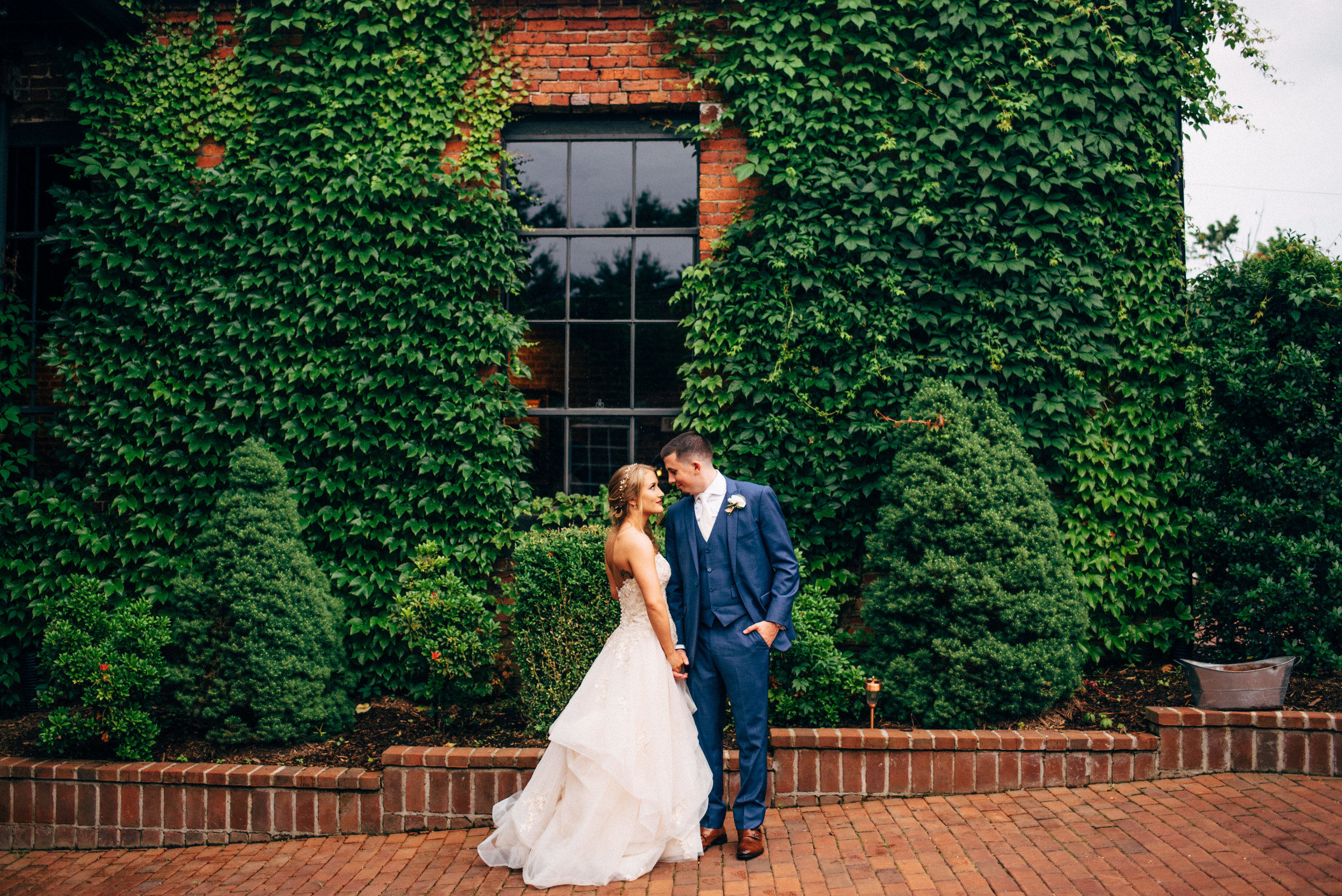 bride and groom looking into each other's eyes in front of ivy covered building